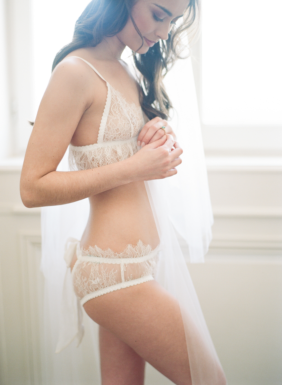 A bride looks at her ring during a boudoir session at Chateau de Varennes; Sylvie Gil Photography