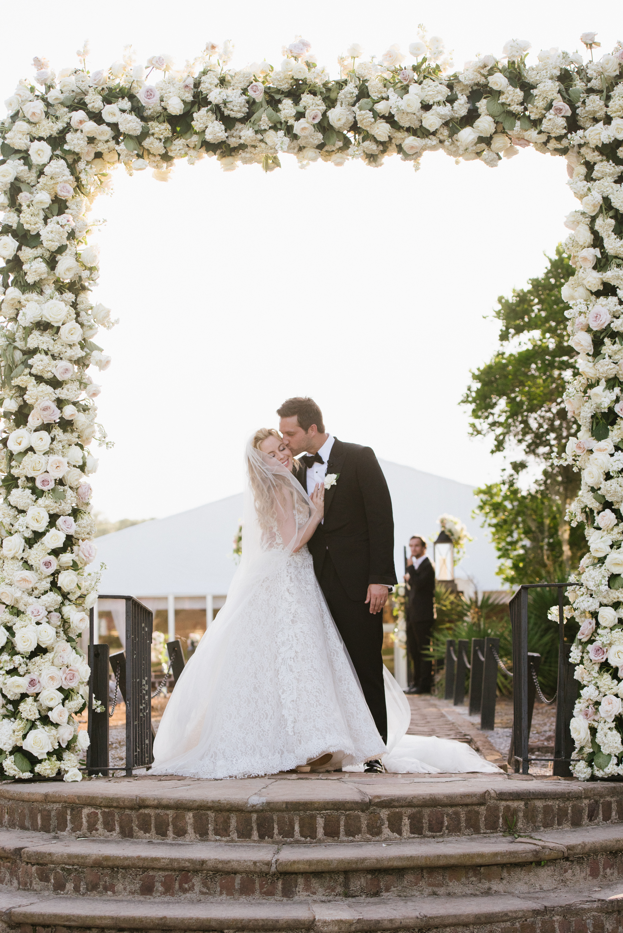 Tara Lipinski and Todd Kapostasy kiss under a floral arch in Charleston after their wedding ceremony; Sylvie Gil Photography