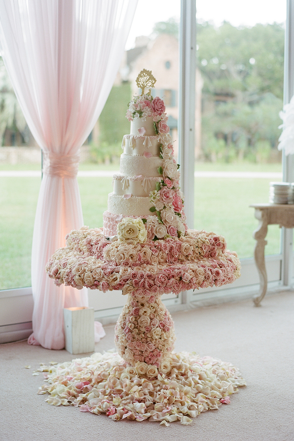 Tara Lipinski's and Todd Kapostasy's seven-tier wedding cake, enrobed with pink and white rose petals; Sylvie Gil Photography