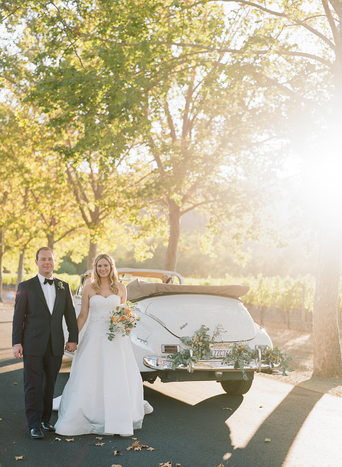 Bride and groom walk hand in hand by a vintage getaway car in Beaulieu Gardens; Sylvie Gil Photography