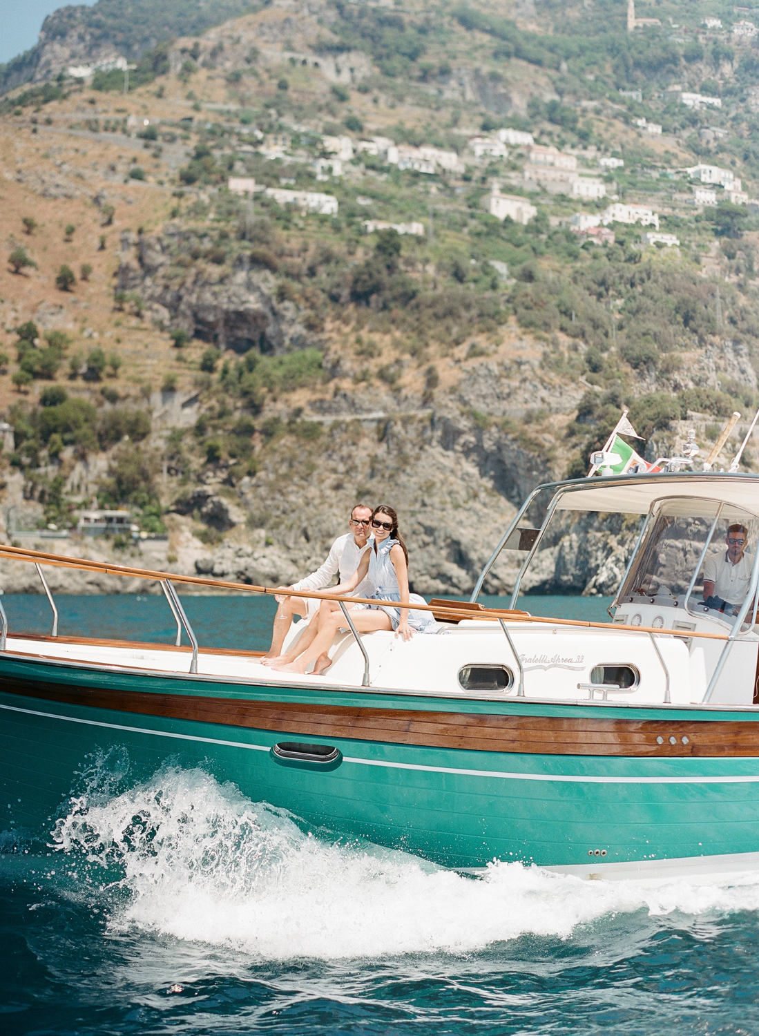 A couple sits on a yacht going to Positano, in the Amalfi Coast, Italy; Sylvie Gl Photography