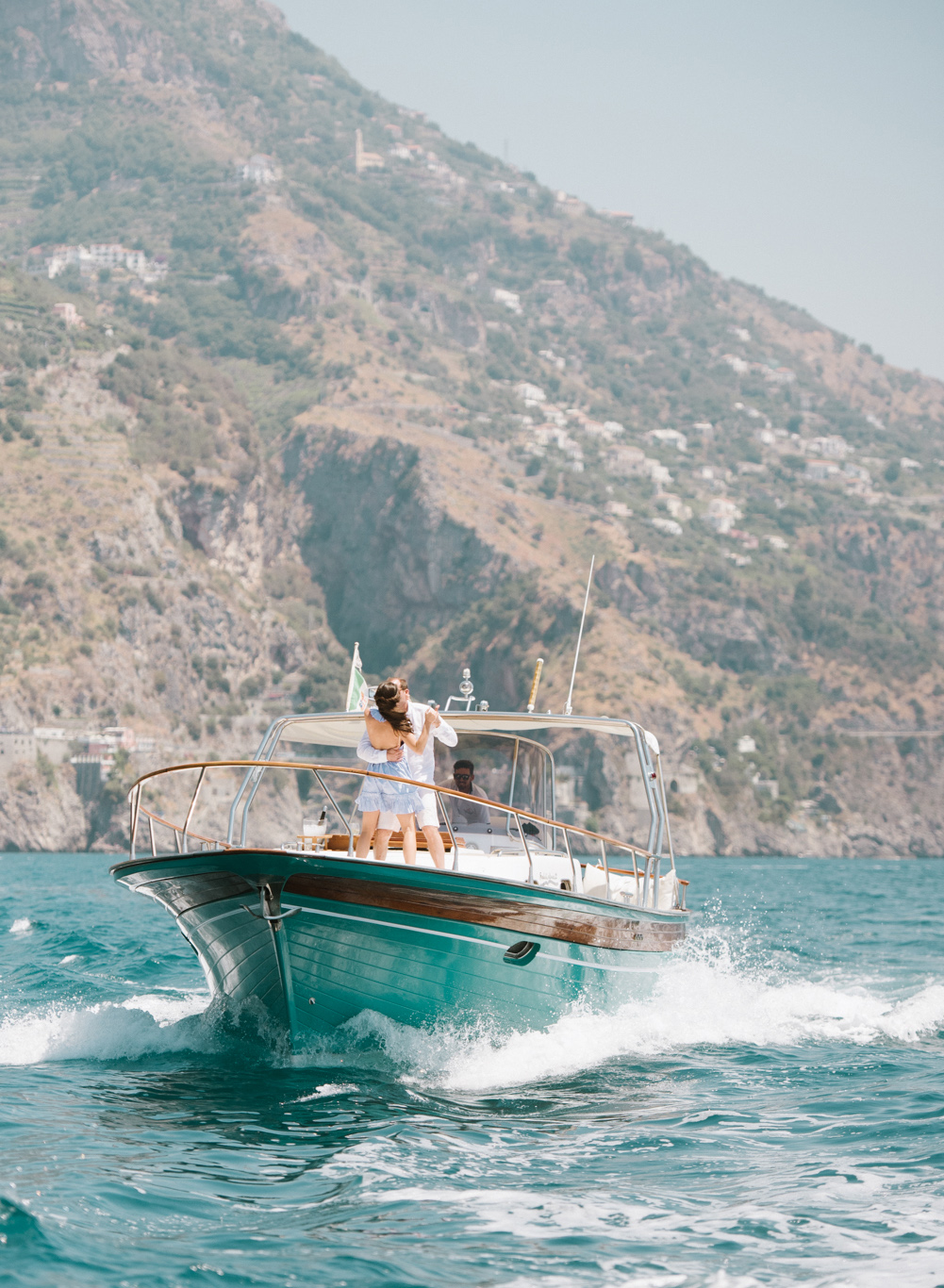 A couple dances on a yacht, traveling to Positano, on the Amalfi Coast; Sylvie Gil Photography