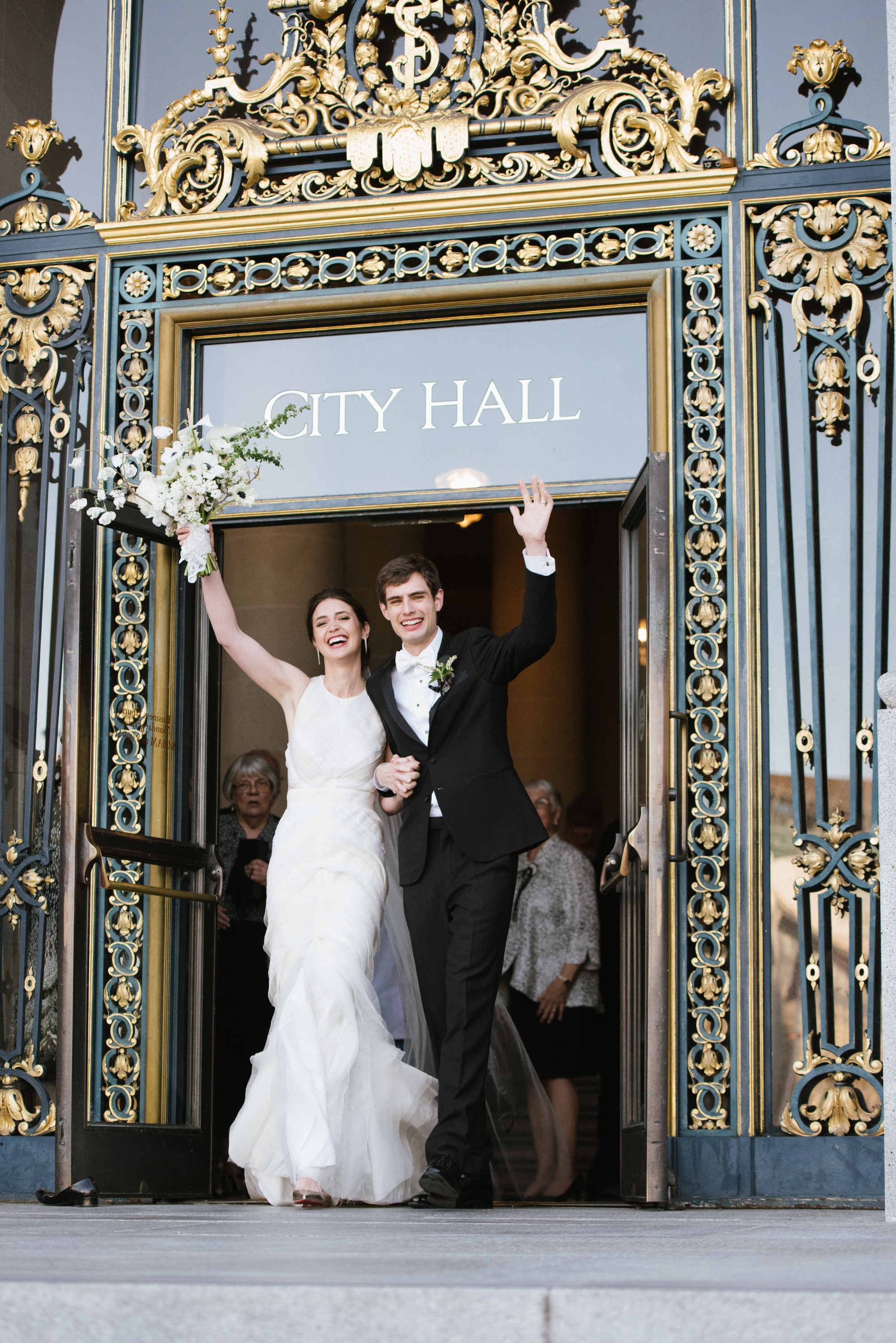 Bride and groom walk out of San Francisco City Hall, just married; Sylvie Gil Photography