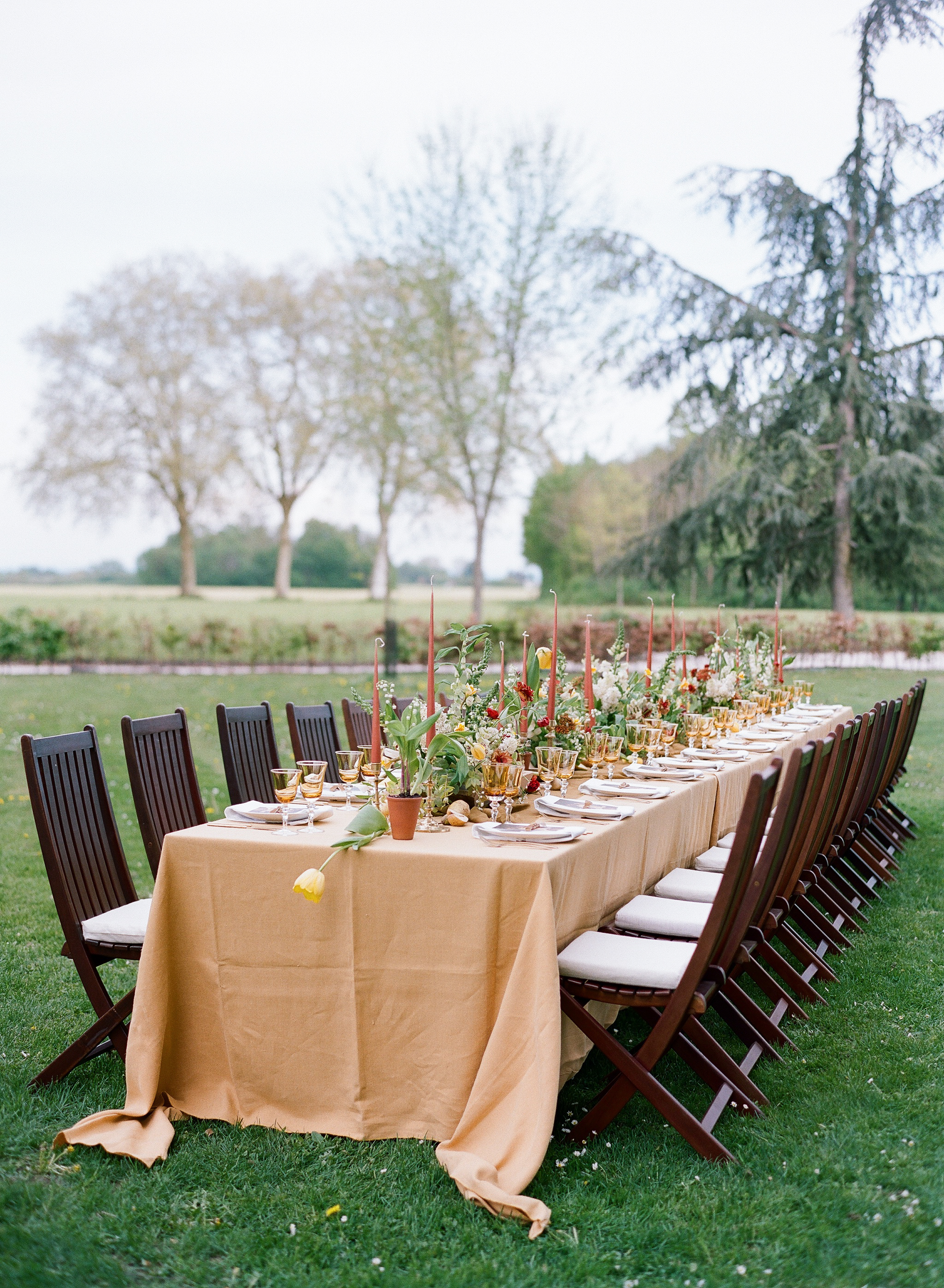 An outdoor reception table decorated with mustard, sage, and burgundy florals; Sylvie Gil Photography