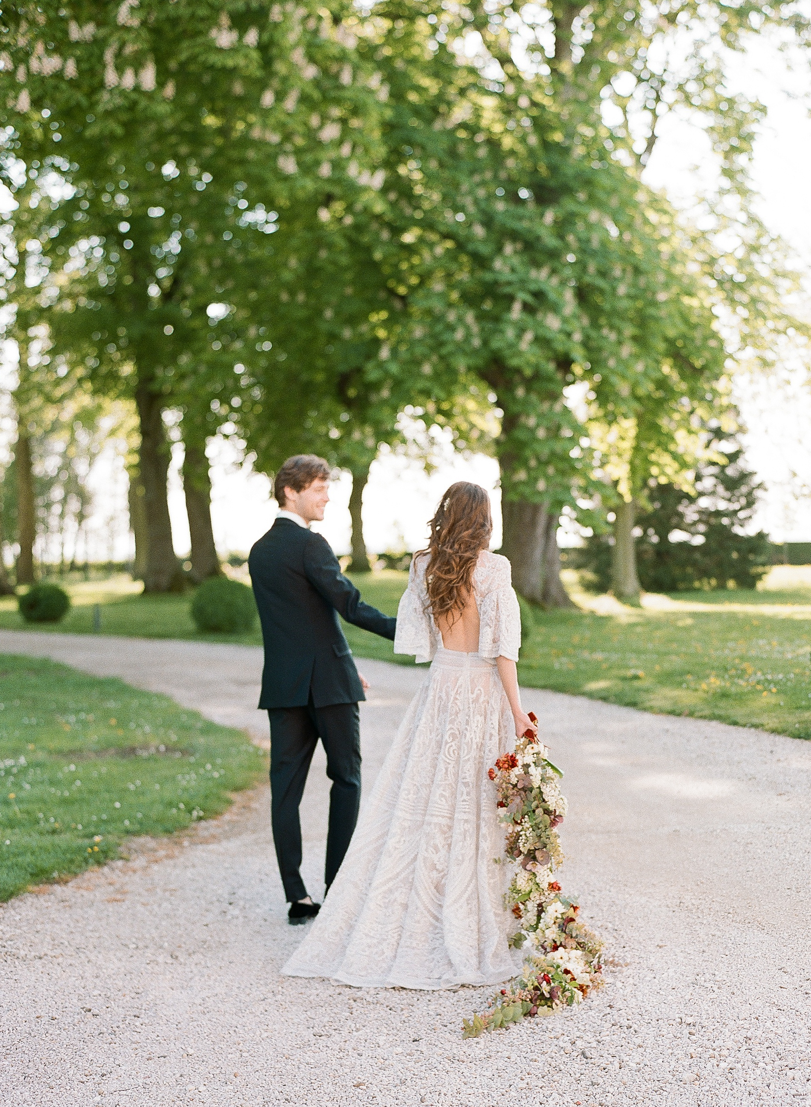 Bride and groom walk into the sunset as she holds a cascading bouquet; Sylvie Gil Photography
