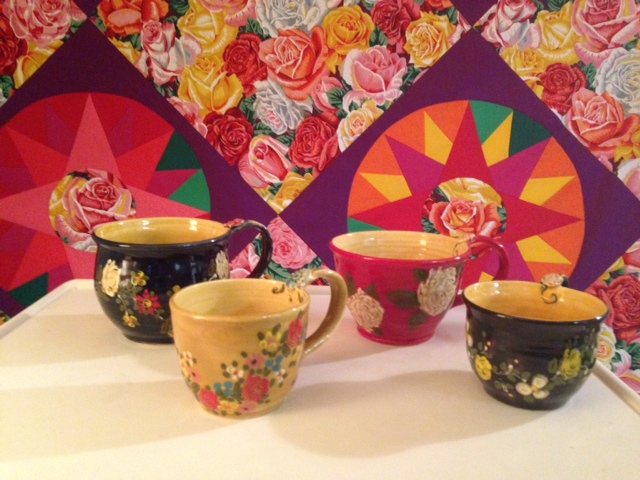 """Mugs we bought from Don Swanson. A new quilt in the background that I am working on called """"Compass Roses""""."""