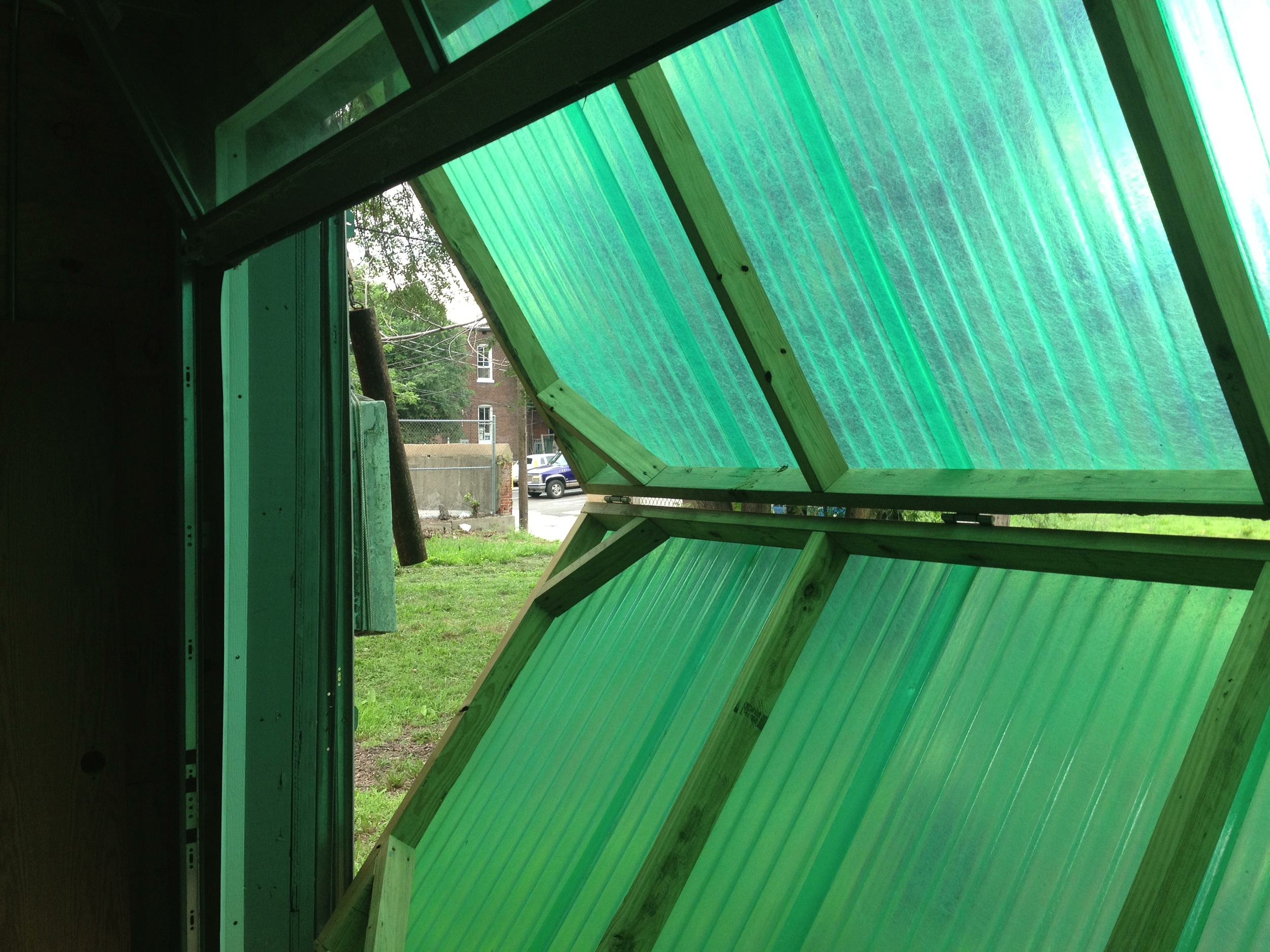The back opening has two layers: a glazed commercial-grade garage door, and a clever outer door made of corrugated greenhouse fiberglass. It operates with homemade concrete counterweights.