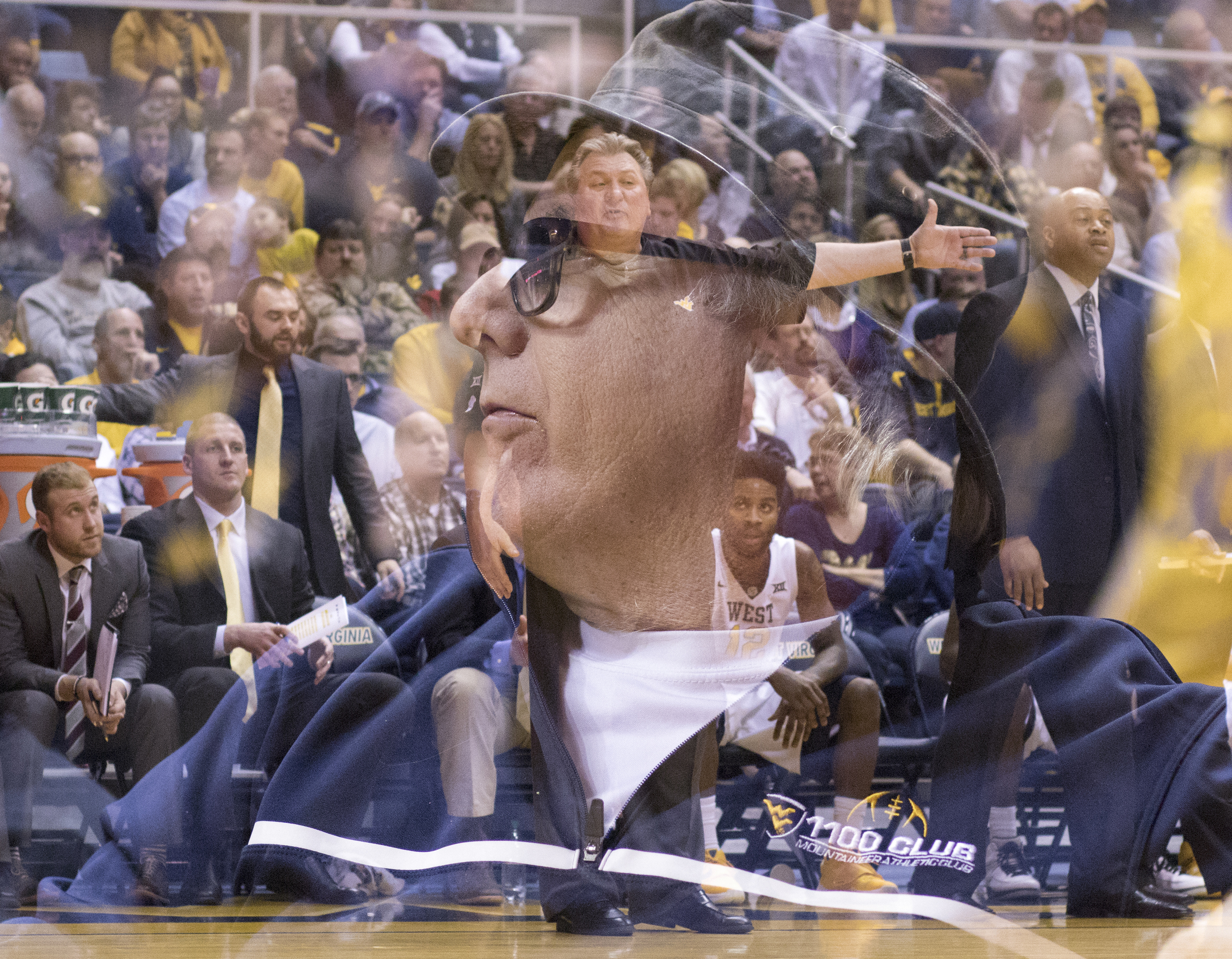 A season ticket holder watches as coach Bob Huggins yells to his team during a stop in action.
