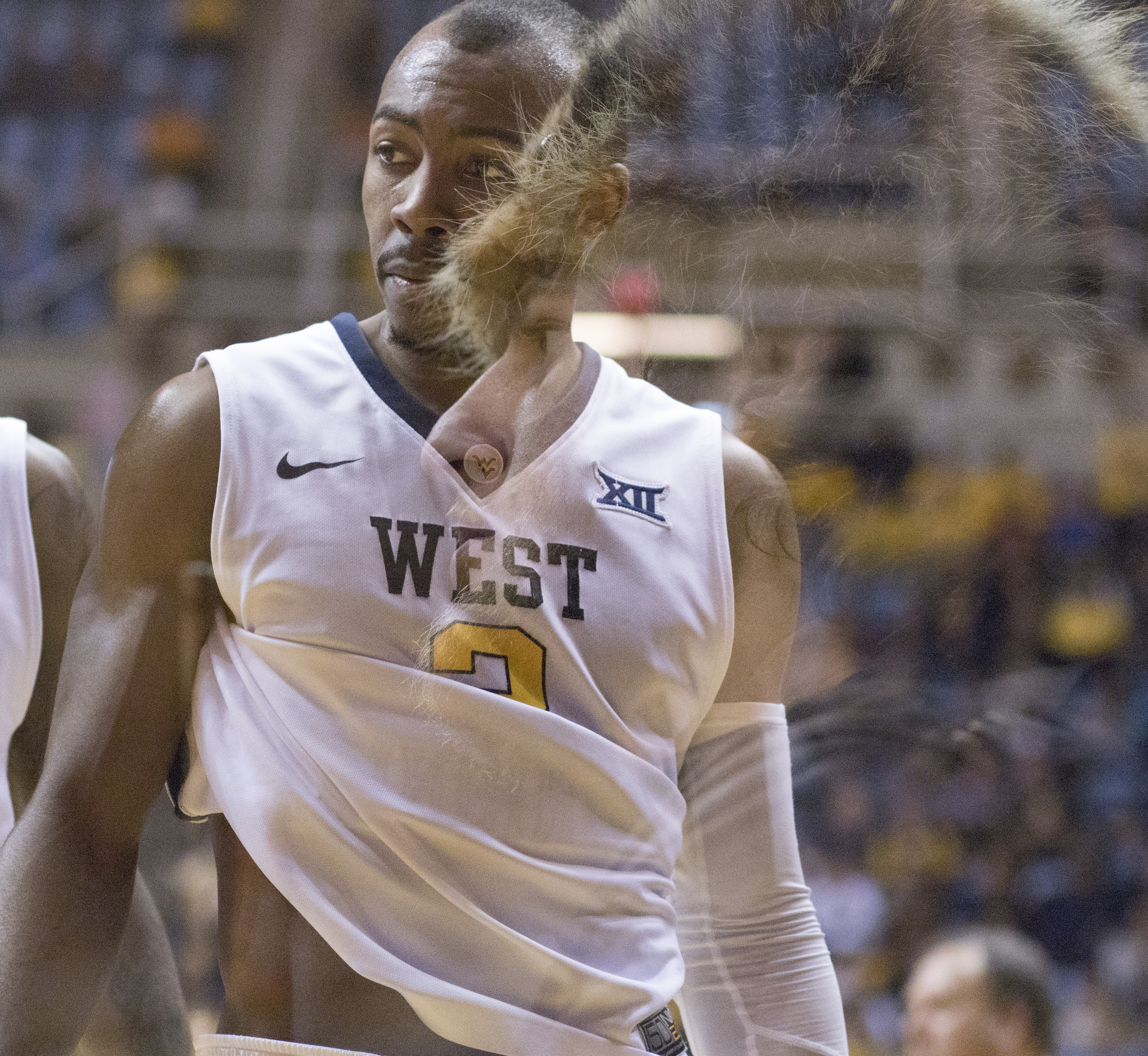 Mountaineer Michael Garcia watches on as Jevon Carter takes a break during a time out.