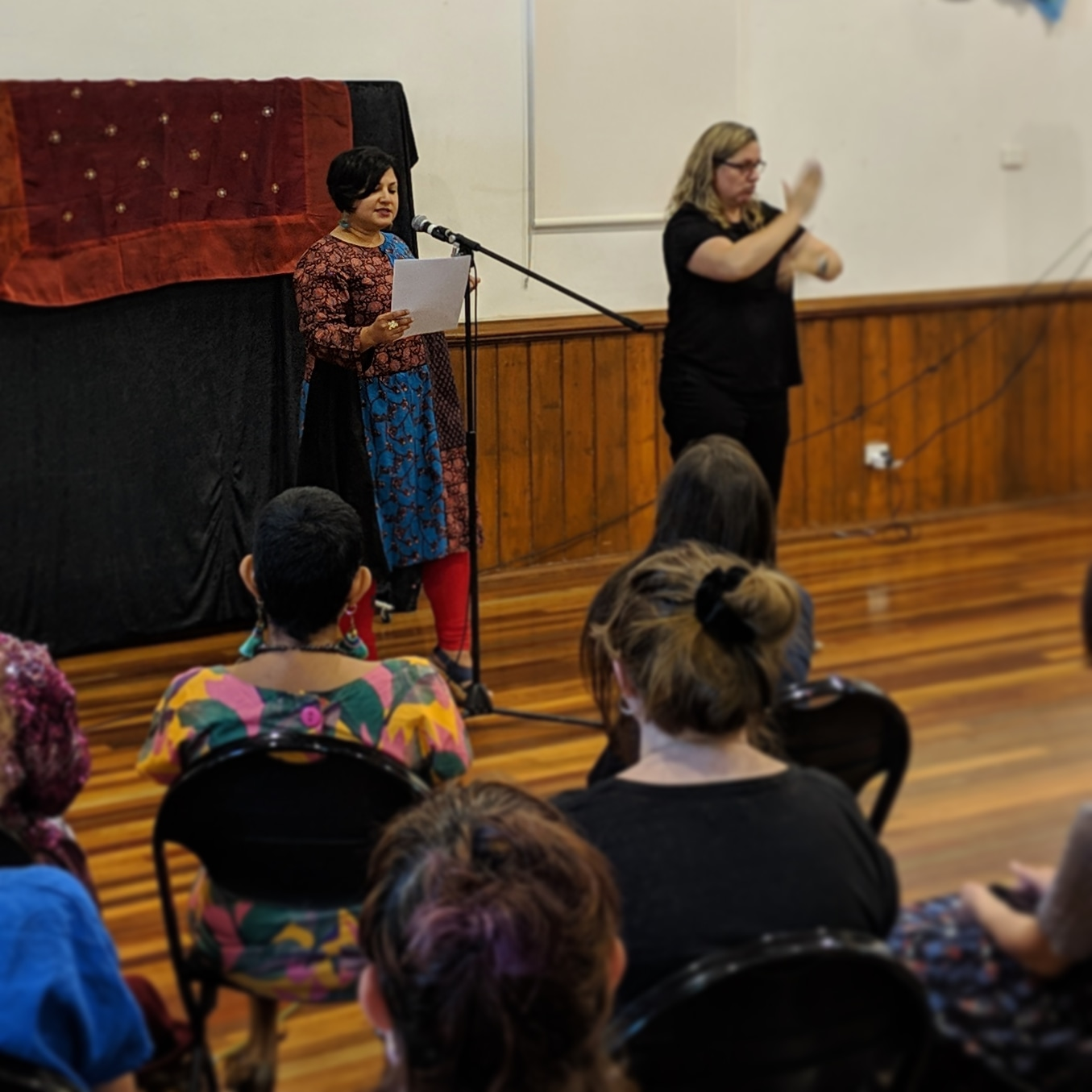 Nadia performing at 'Love Letters of Feminisms', alongside an  Auslan  interpreter