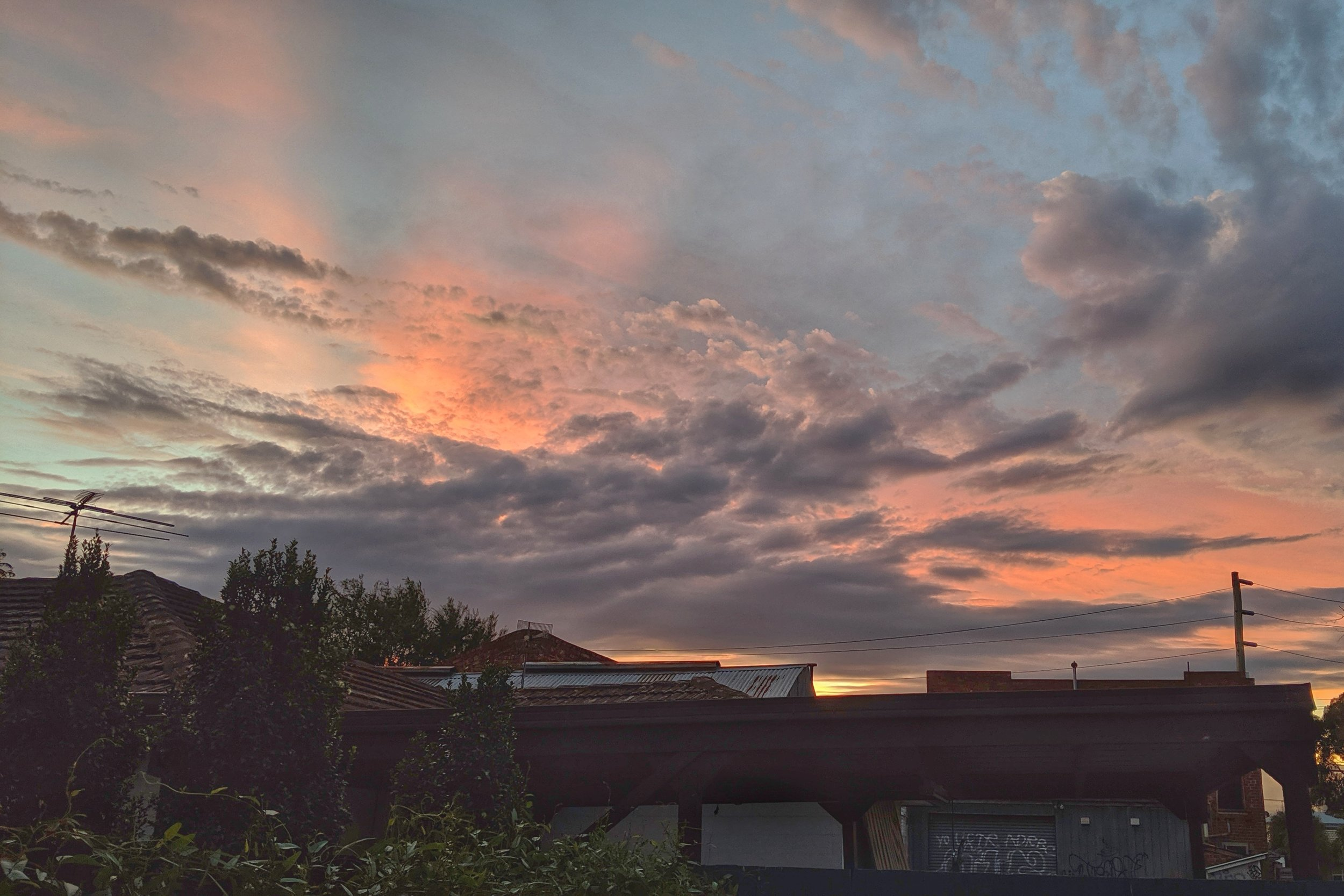Peach-pink sunset behind the clouds, above the rooftops.