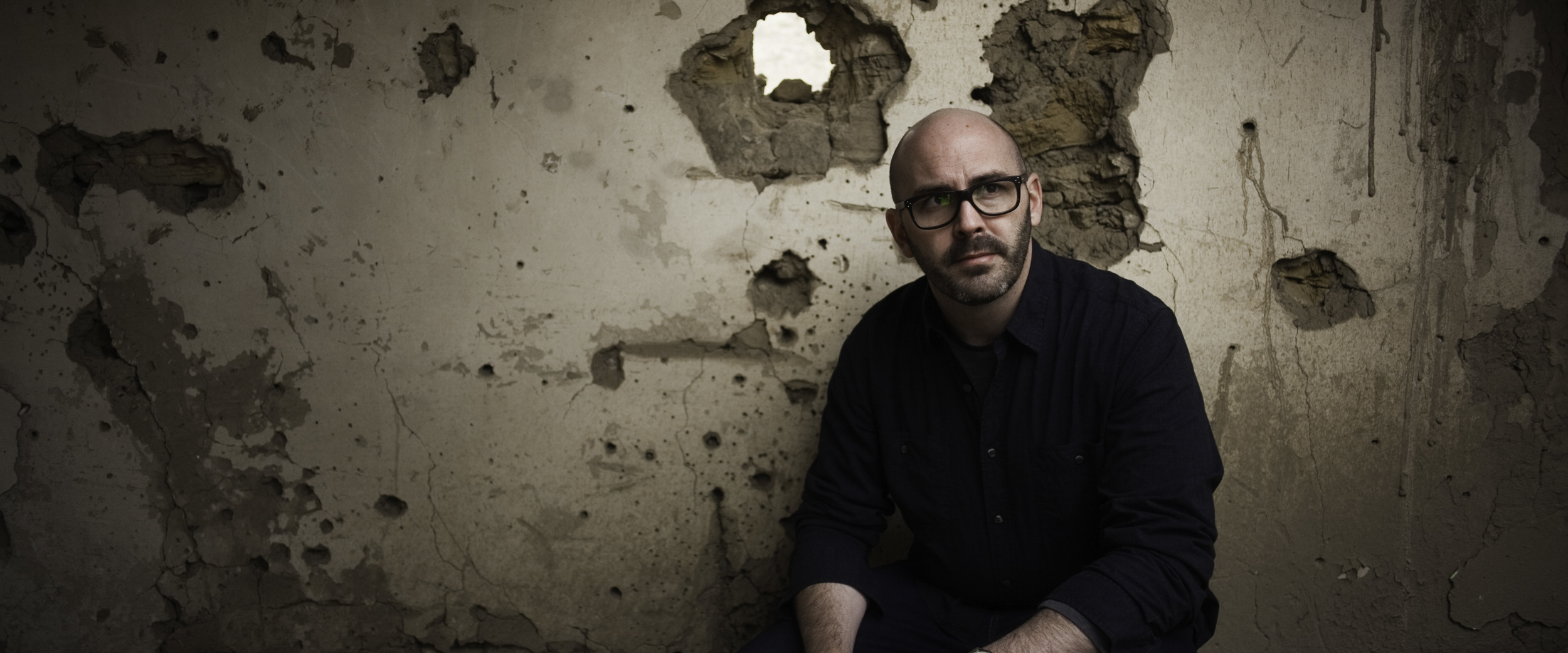 Director Jesse Gustafson poses against a war-torn wall