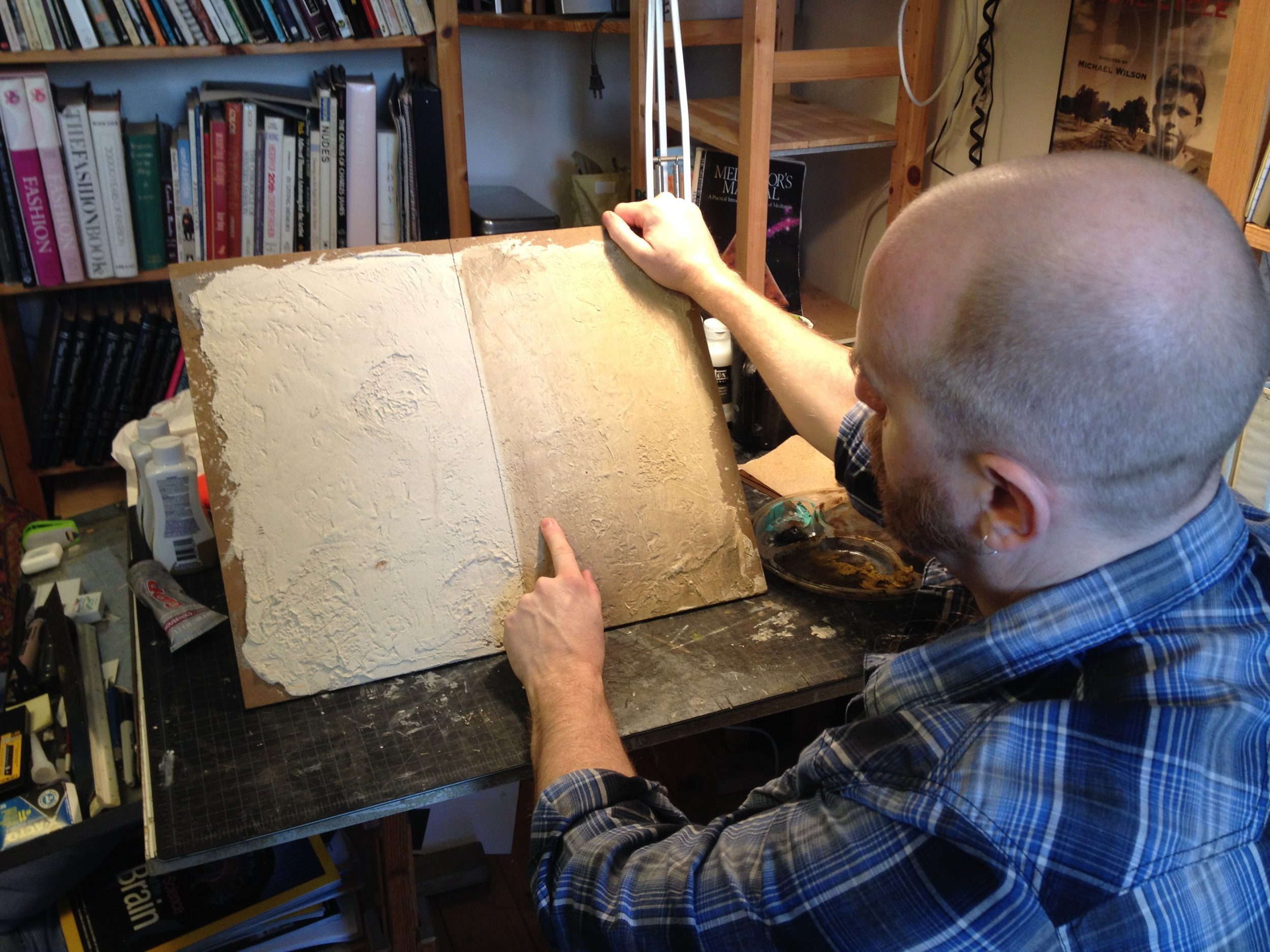 Production Designer David M. Barber goes over various wall treatments in his studio.