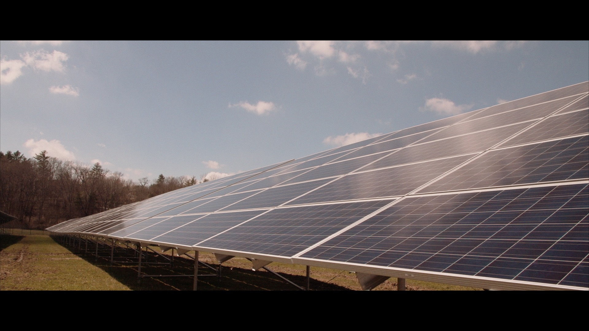 A screen grab of a shot we did of one of the rows of the array at Houghton College. Thanks to Borrego Solar, this solar array will be one of the largest solar arrays in an American college campus. Here, we set the FS700 filming a bit of a long shot on a tripod, so that we can speed it up in editing/post and capture the reflection of the clouds moving across the array. It's one simple way of adding interest to what typically can be a pretty cold mechanical shot, and it works really well for this perspective. We are also playing with lines to add a more dynamic and richer depth to this shot.