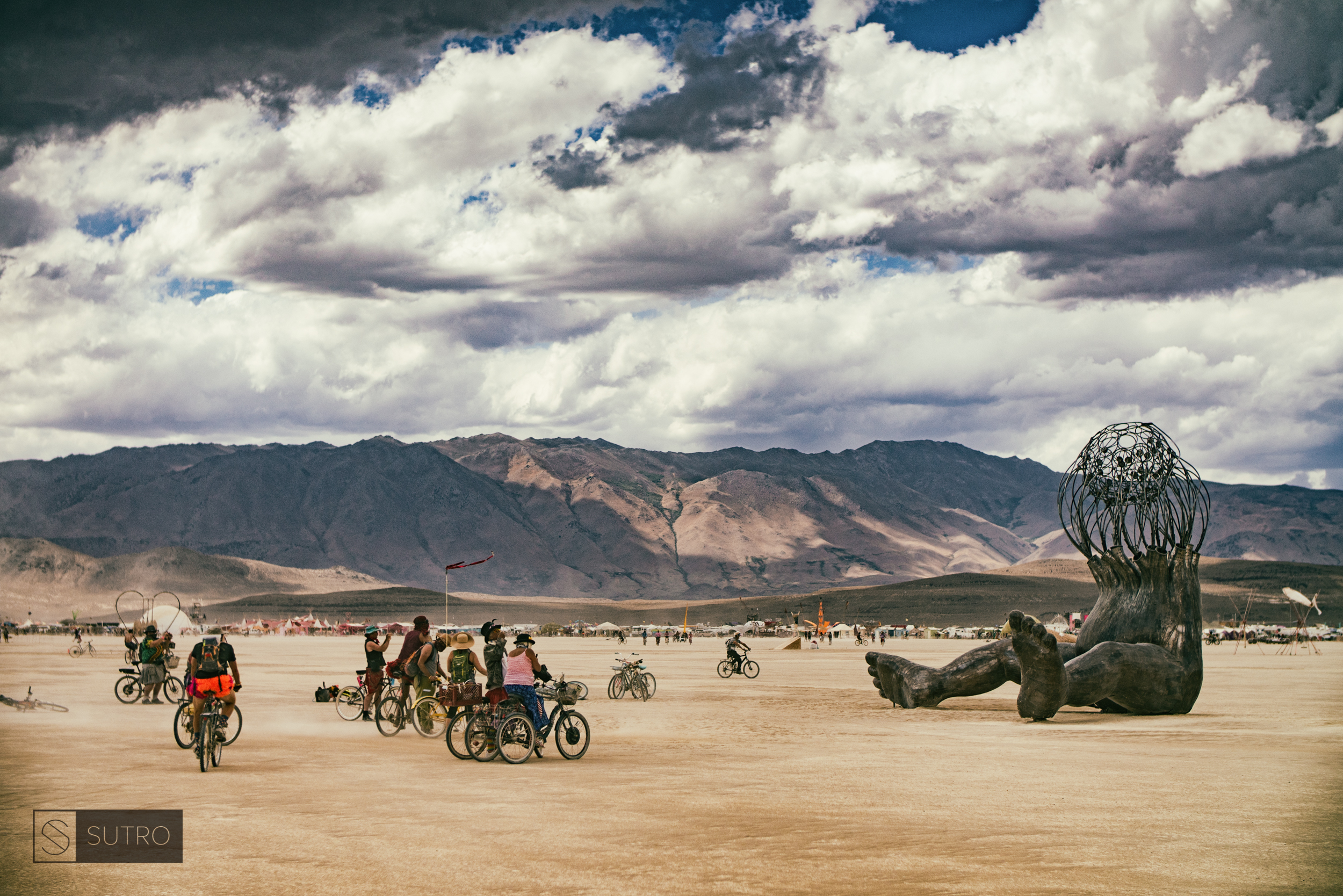 """Burners admire on the many pieces of artwork on the Playa, this one by Michael Christian called """"Brainchild""""."""