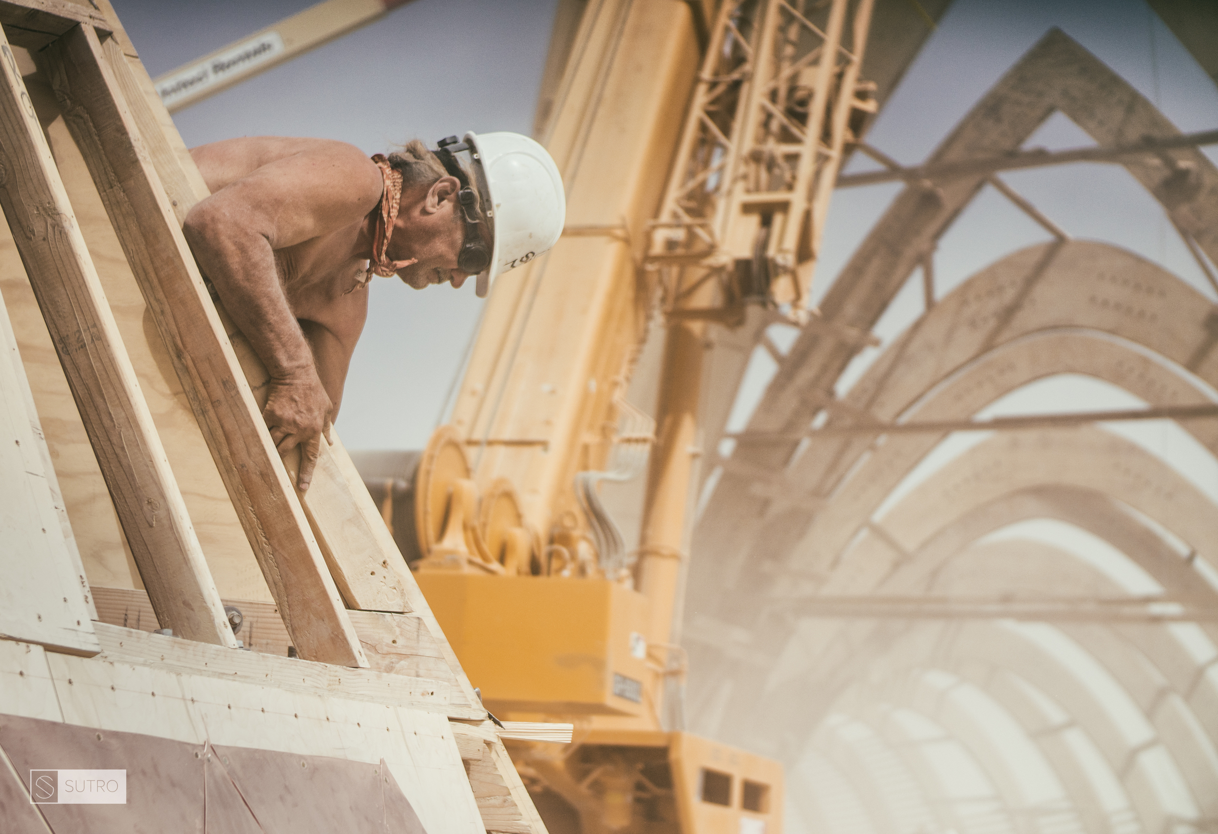 Jan Yoder, aka. Spyreman, is seen here working on the top piece of the Temple, with the rest of the structure disappearing through the dust in the background.