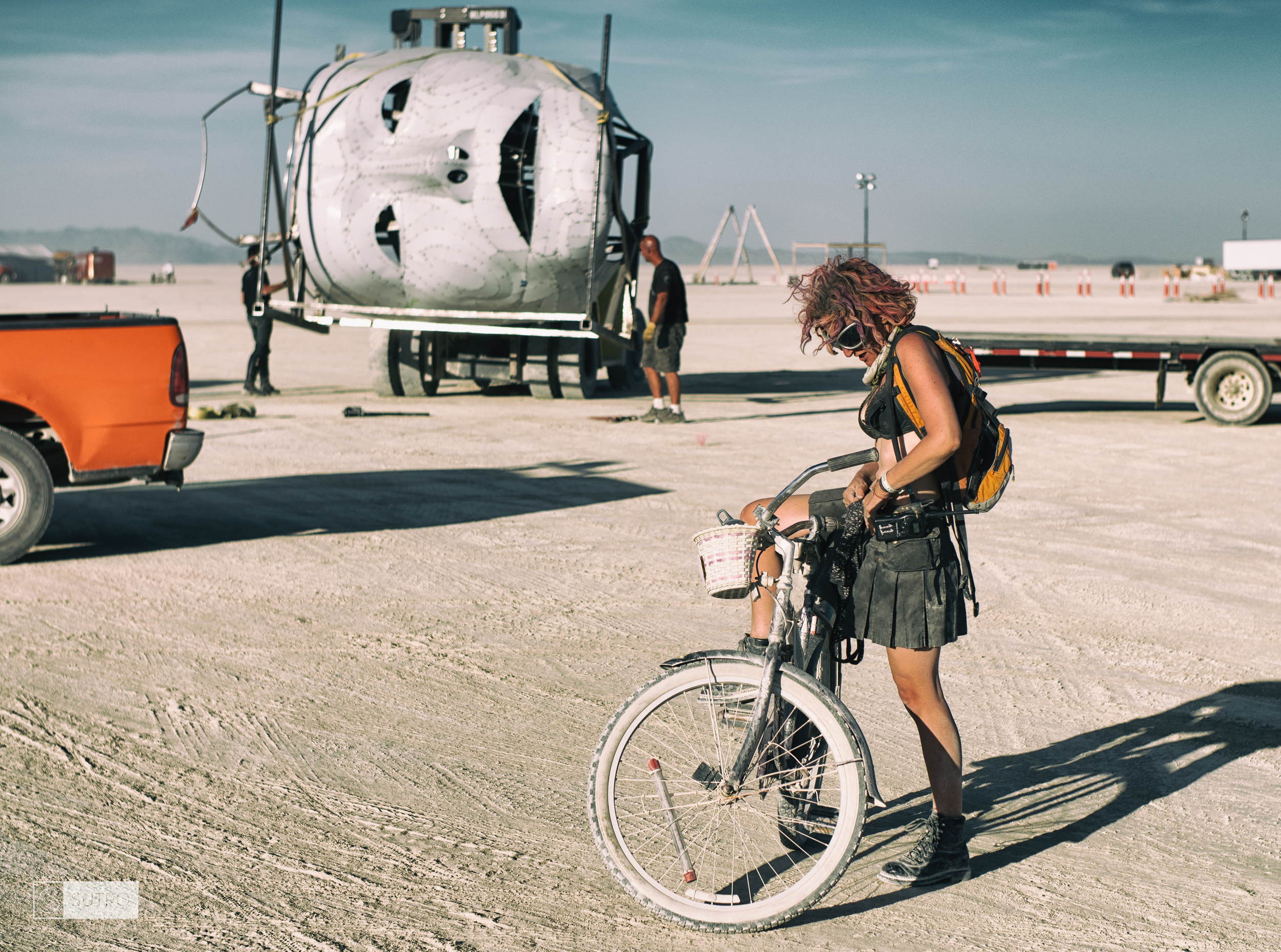 Mango, on her bike, while crew members from the Medusa art piece transport the head.