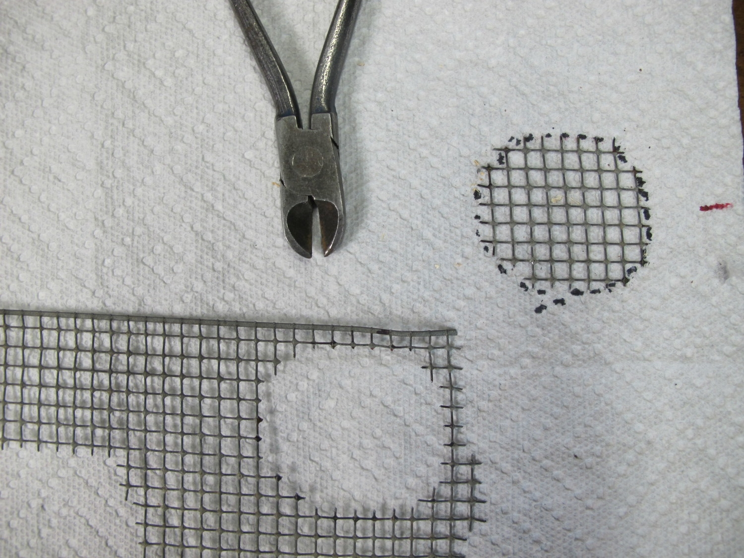 Wire mesh circular bottom cut out of wire mesh stock.