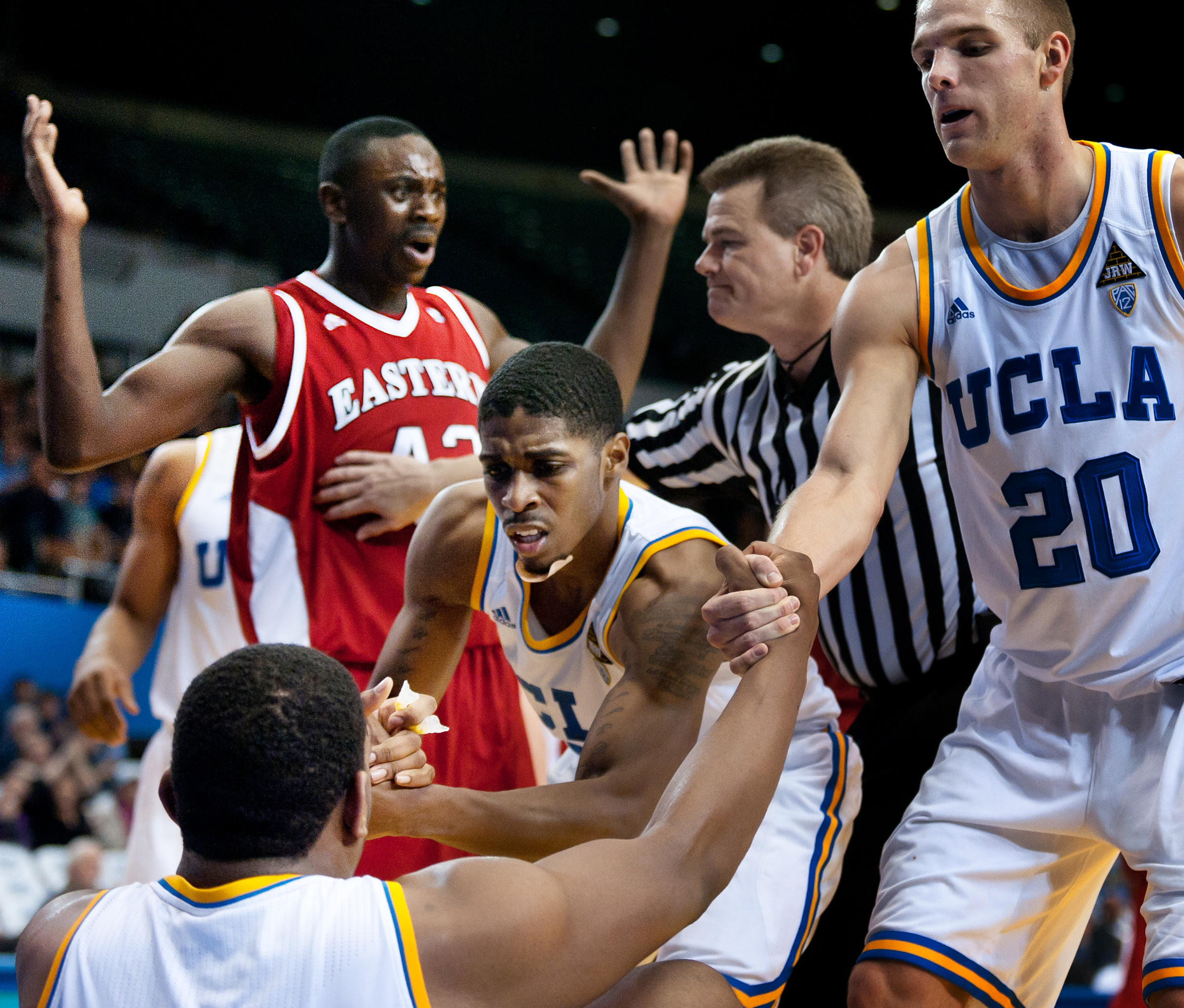 LOS ANGELES, CA – Senior guard Lazeric Jones (left) and junior forward Brendan Lane (right) help sophomore center Joshua Smith back to his feet after Smith was fouled to the ground by Eastern Washington senior forward Cliff Ederaine at the Los Angeles Sports Arena on Wednesday, December 14, 2011.