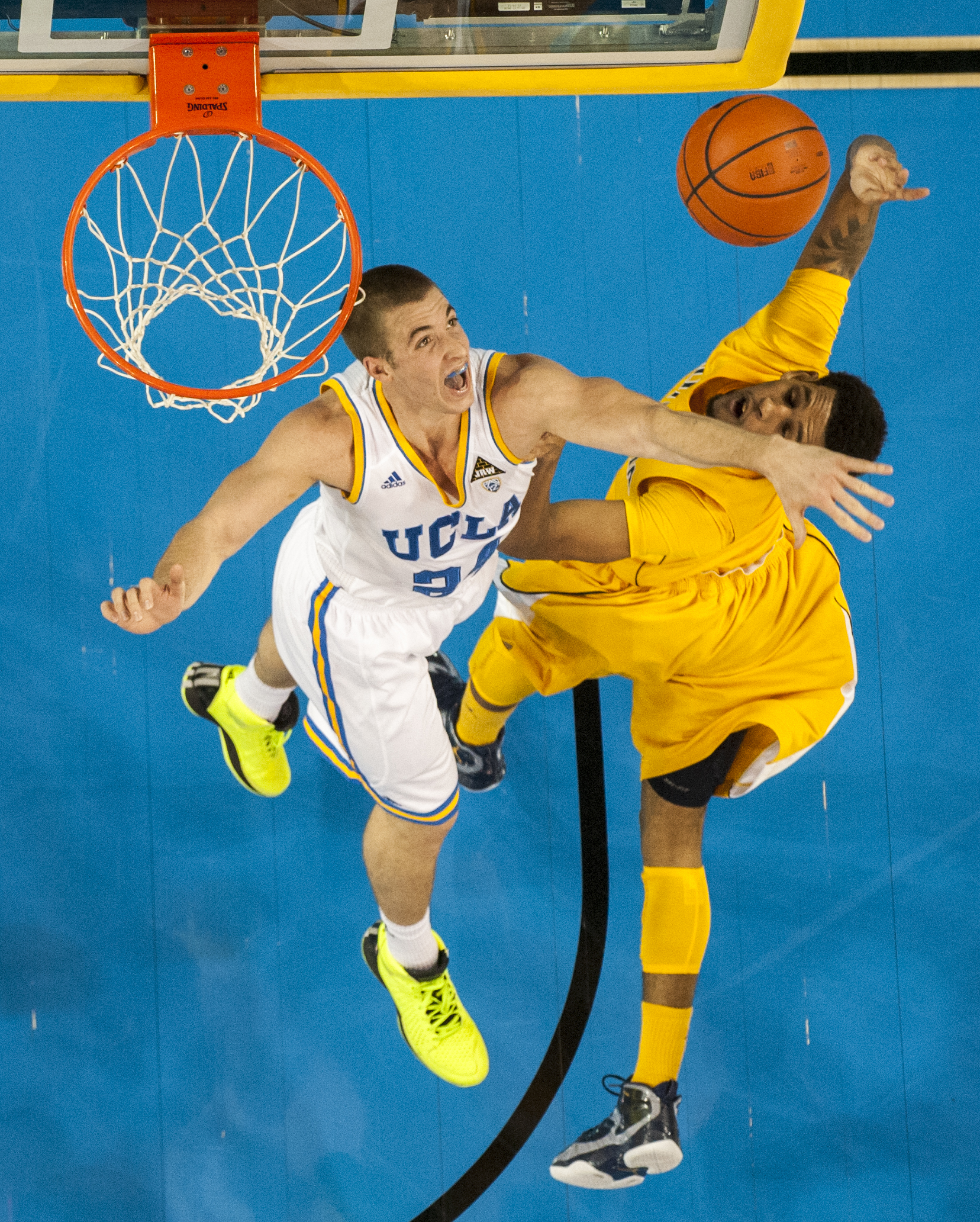 LOS ANGELES, CA – Redshirt junior forward Travis Wear blocks a layup by Cal Bears sophomore forward Christian Behrens at Pauley Pavilion on Thursday, January 3, 2013.