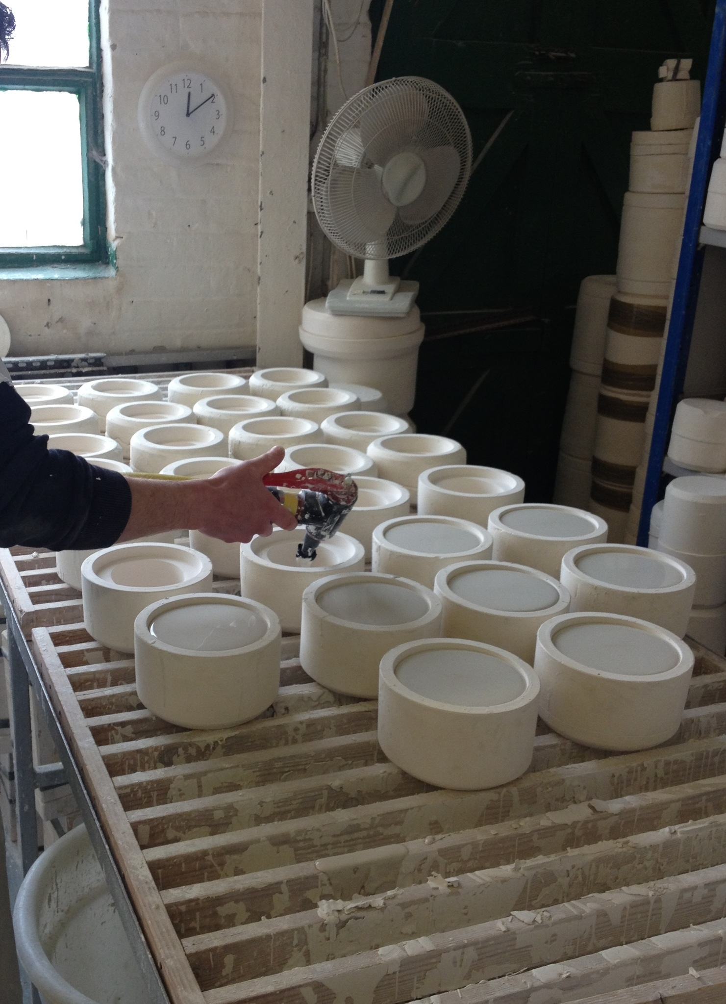 The slip cast bowl moulds being filled with the liquid bone china slip