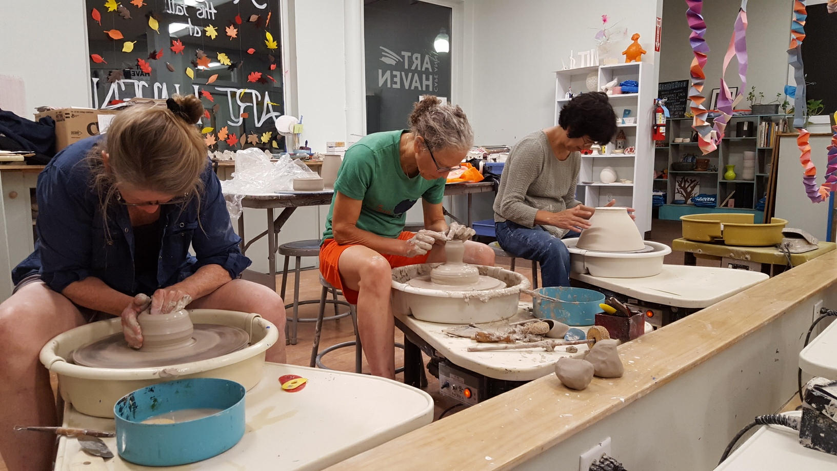 Ruth Worall (on the right) leads her class in creating work on the Potter's Wheel.