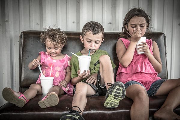 Three kids eating snowballs in Lockport, Louisiana.