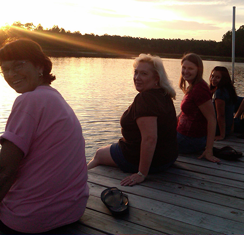 A-Group-of-ladies-sitting-on-a-dock-by-the-water