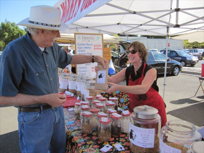 """Susie Falbo sells a bag of granola recently to Al Lockwood of Cotati, a regular customer at the farmers market. """"This is the best granola on the planet,"""" Lockwood said. """"It's a meal unto itself."""""""