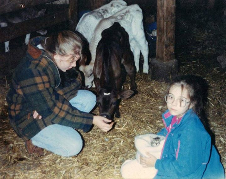 "A photo my sister, Sara, posted on my wall today in honor of my birthday: ""This is one of my favorite pictures of us. It feels like a bunch of our childhood memories in one fantastic picture. There are baby cows and kittens, and we are at the dairy farm next door to my grandparent's place in Millersburg, Ohio. Also, Aimee and I look fabulous. I miss you baby sister! I wish we got together more."""