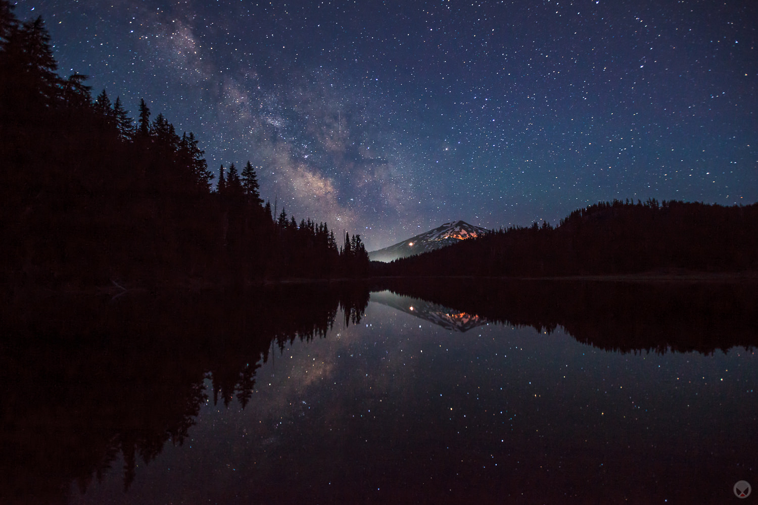 The Milky Way lands in the parking lot of Mount Bachelor's ski resort and is reflected in Todd Lake.