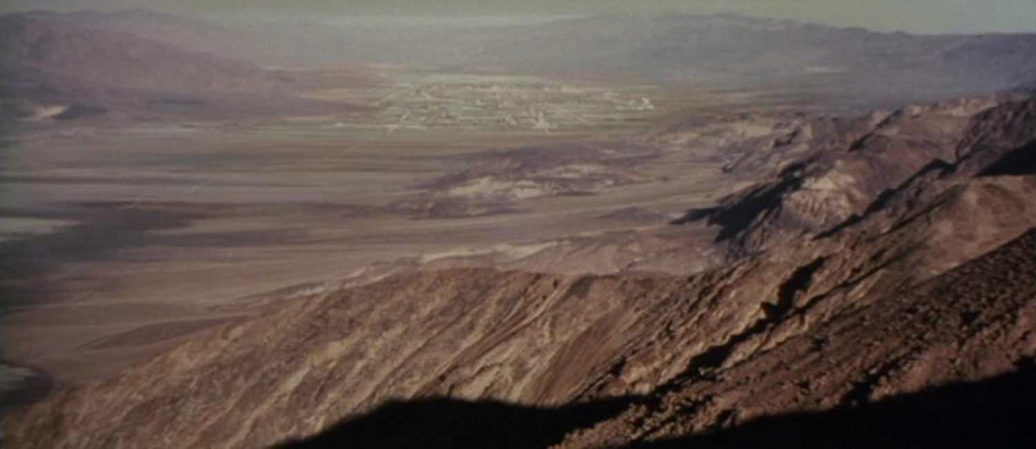 EXT. TATOOINE - BLUFF OVERLOOKING MOS EISLEY SPACEPORT - DAY