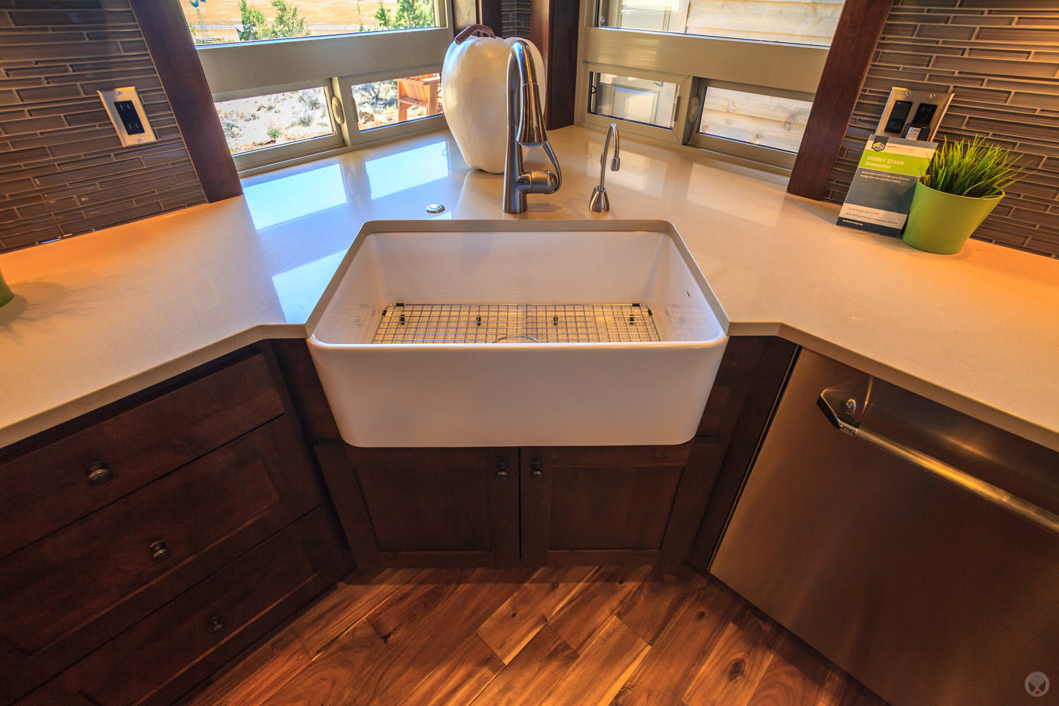 A porcelain farm sink. Also note: Shaker-style cabinets, stainless steel appliances, and subway tile backsplash.