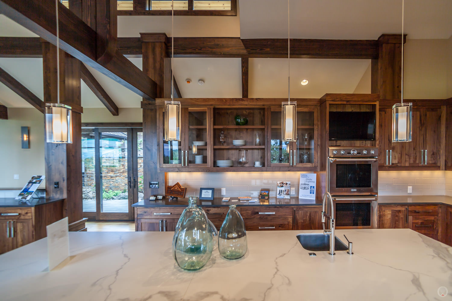 Pendant light fixtures.Also note: Shaker-style cabinets, stainless steel appliances, and subway tile backsplash.