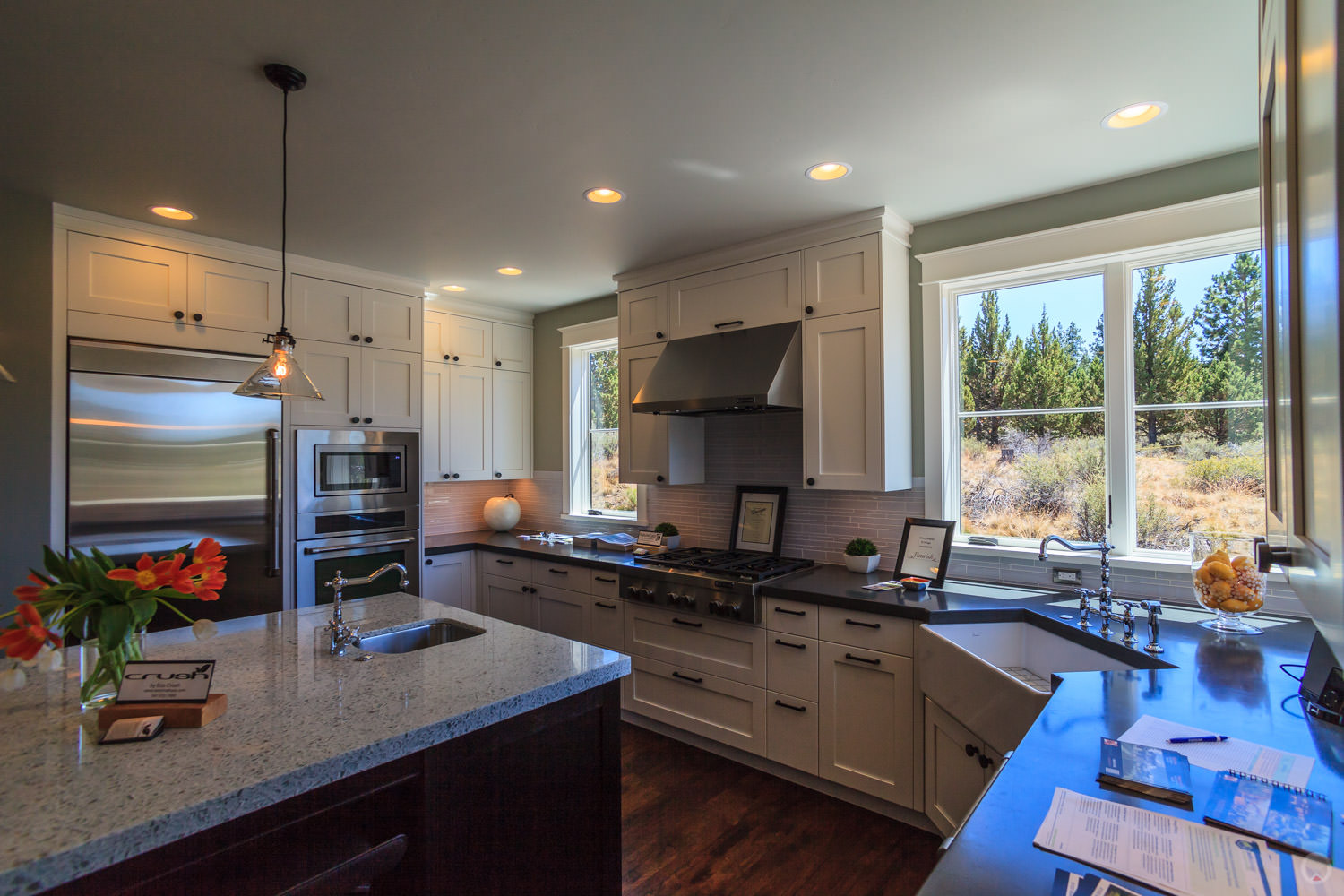 Stainless steel appliances.Also note: Shaker-style cabinets, subway tile backsplash, farm sink, and pendant light fixture.