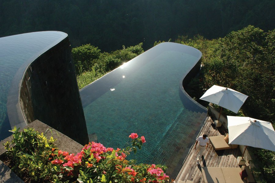 UBUD HANGING GARDENS BALI, INDONESIA  Perched on a steep embankment next to terraced rice fields that overlook the lush Ayung river gorge, this Orient-Express hotel consists of 38 Balinese-style villas that appear to float down the hillside. Just as dramatic is its split-level infinity pool, designed by the French architect Gordon Shaw. Lined with Batu Chandi volcanic stone and consisting of geometric walls of solidified volcanic ash, the striking bi-level pool is suspended over a dense rainforest, with an undulating shape that echoes the surrounding terrain.  ubudhanginggardens.com