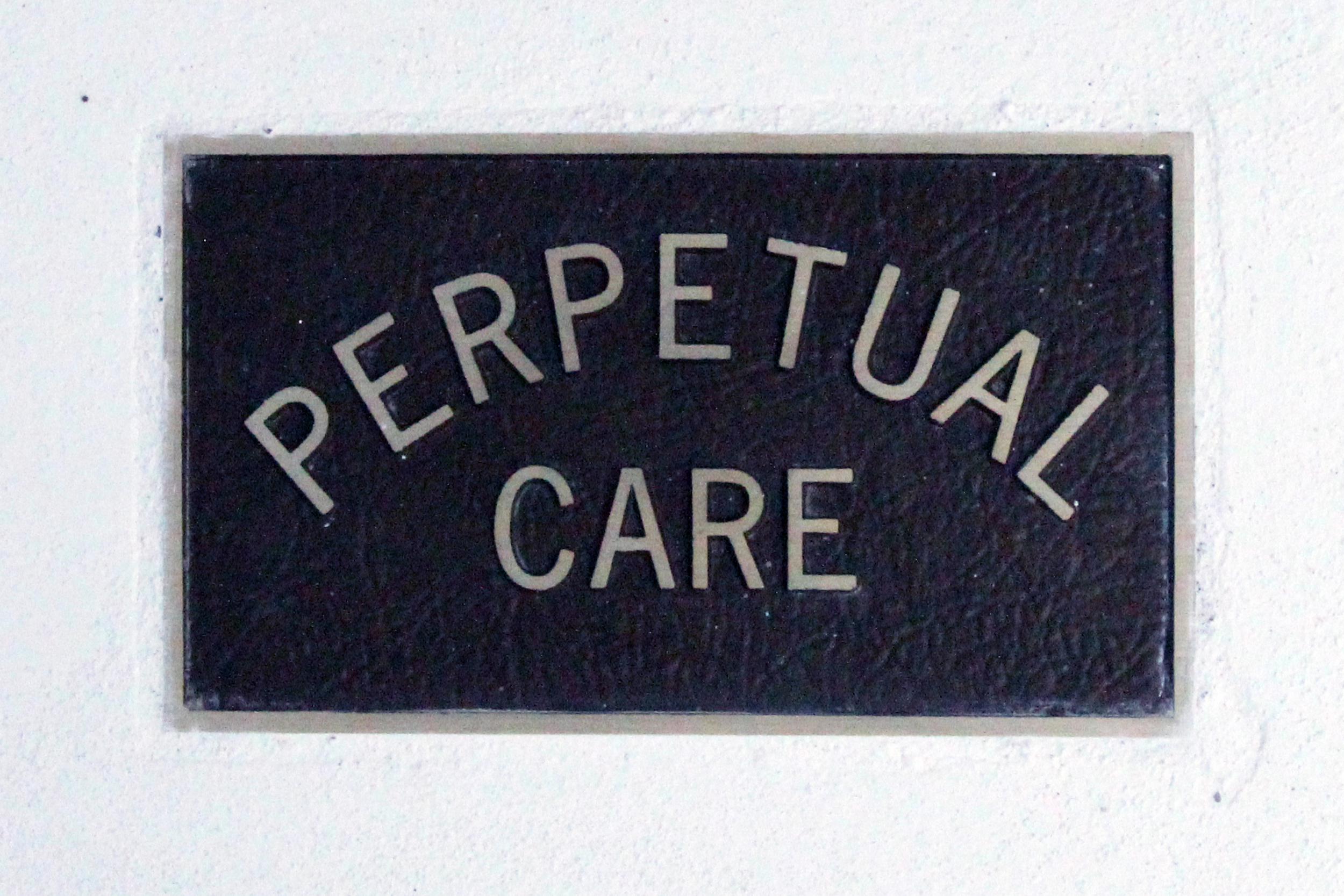 Perpetual care placard, indicating the deceased or their family has paid for the tomb to be kept up for the infinite future