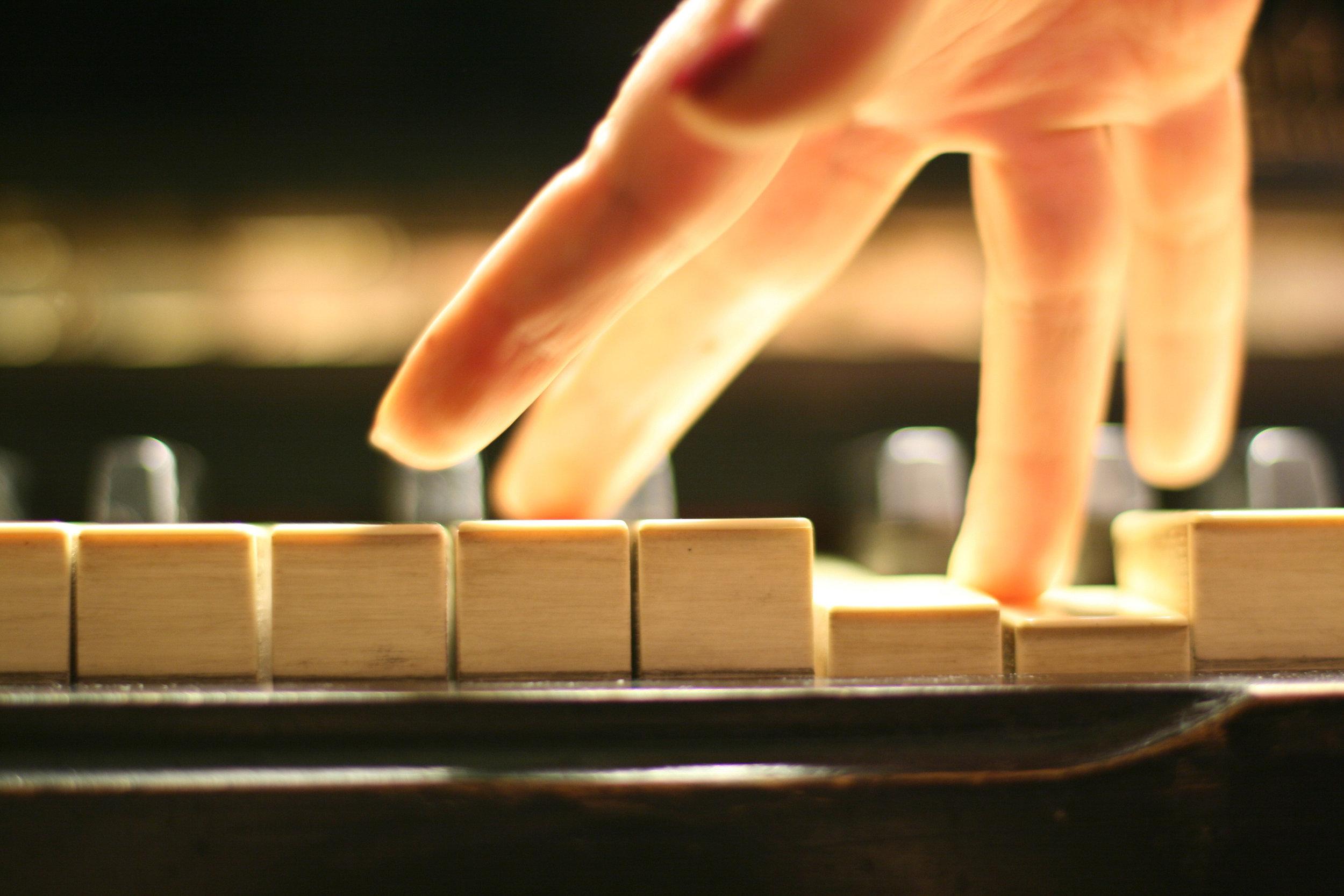 Hand playing piano chord.jpg