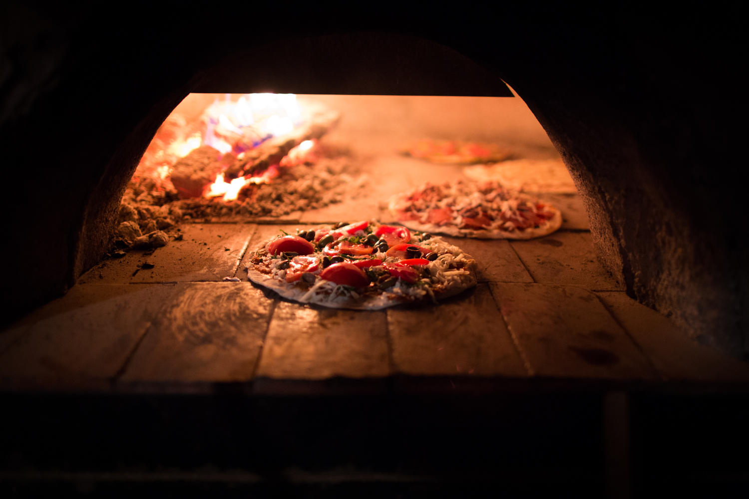 pizzas in the wood oven