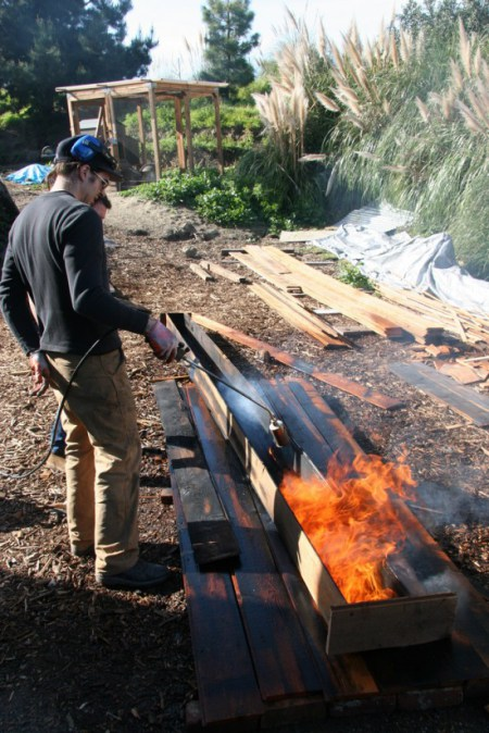 Jay ignites the planks with a roofing torch.