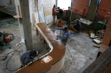Concrete is a challenging medium-heavy, difficult to mix, (especially with additives) and tricky to achieve consistent finishes. The mold construction must be spot on because every blemish shows and the molds must be strong enough to withstand the vibration process. Vibration consolidates concrete in two stages: first by moving the concrete particles, then by removing entrapped air.