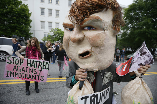 JIM BOURG / REUTERS  A masked protester demonstrates outside Republican National Committee (RNC) headquarters, where Republican U.S. presidential candidate Donald Trump was meeting with House Speaker Paul Ryan (R-WI) and RNC Chairman Reince Priebus in Washington, U.S., May 12, 2016.