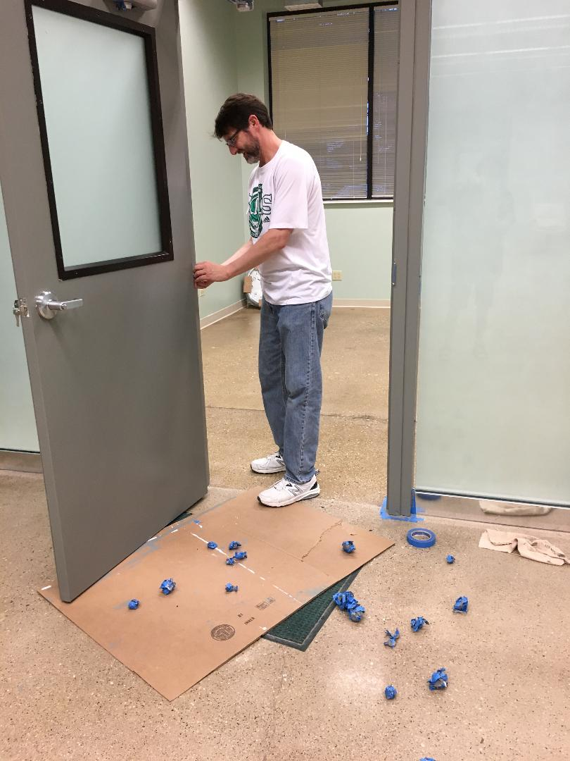 Removing tape from the freshly painted doors.