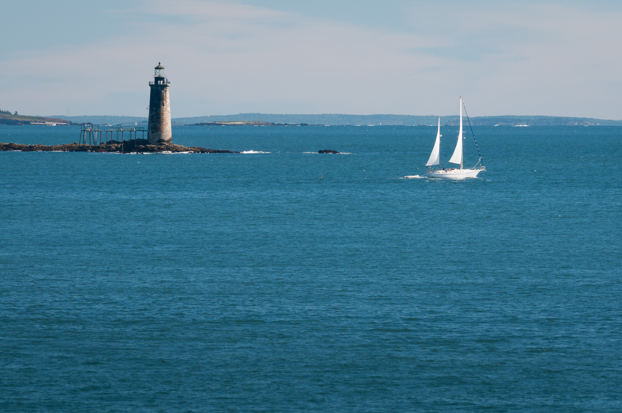 Ram Island Ledge Light, in Maine, with white sailboat in foreground