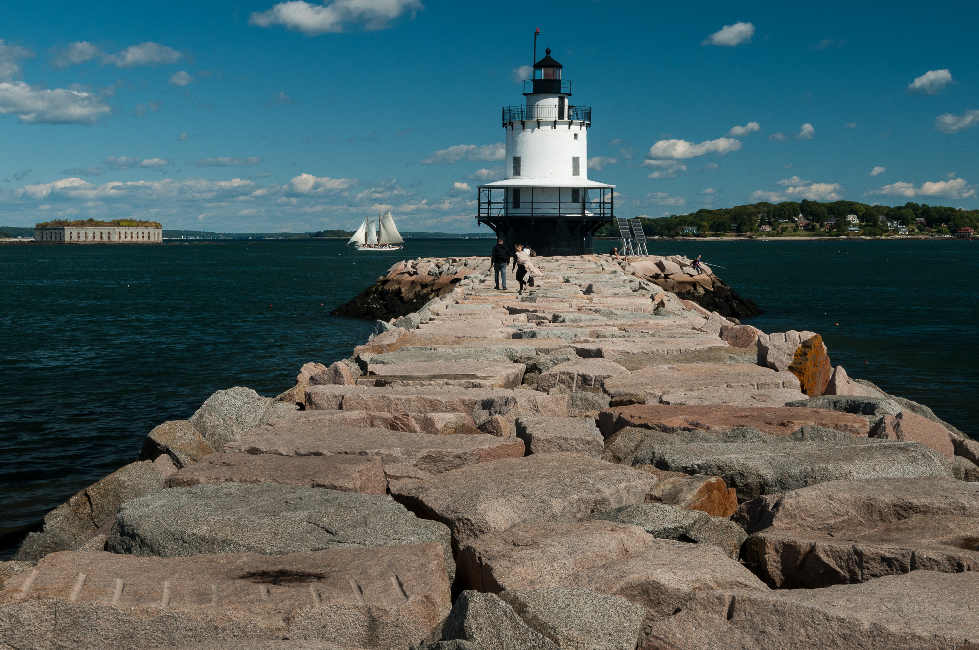Spring Point Ledge Light, in South Portland, Maine, with view of Fort Gorges and white sailboat in the bay
