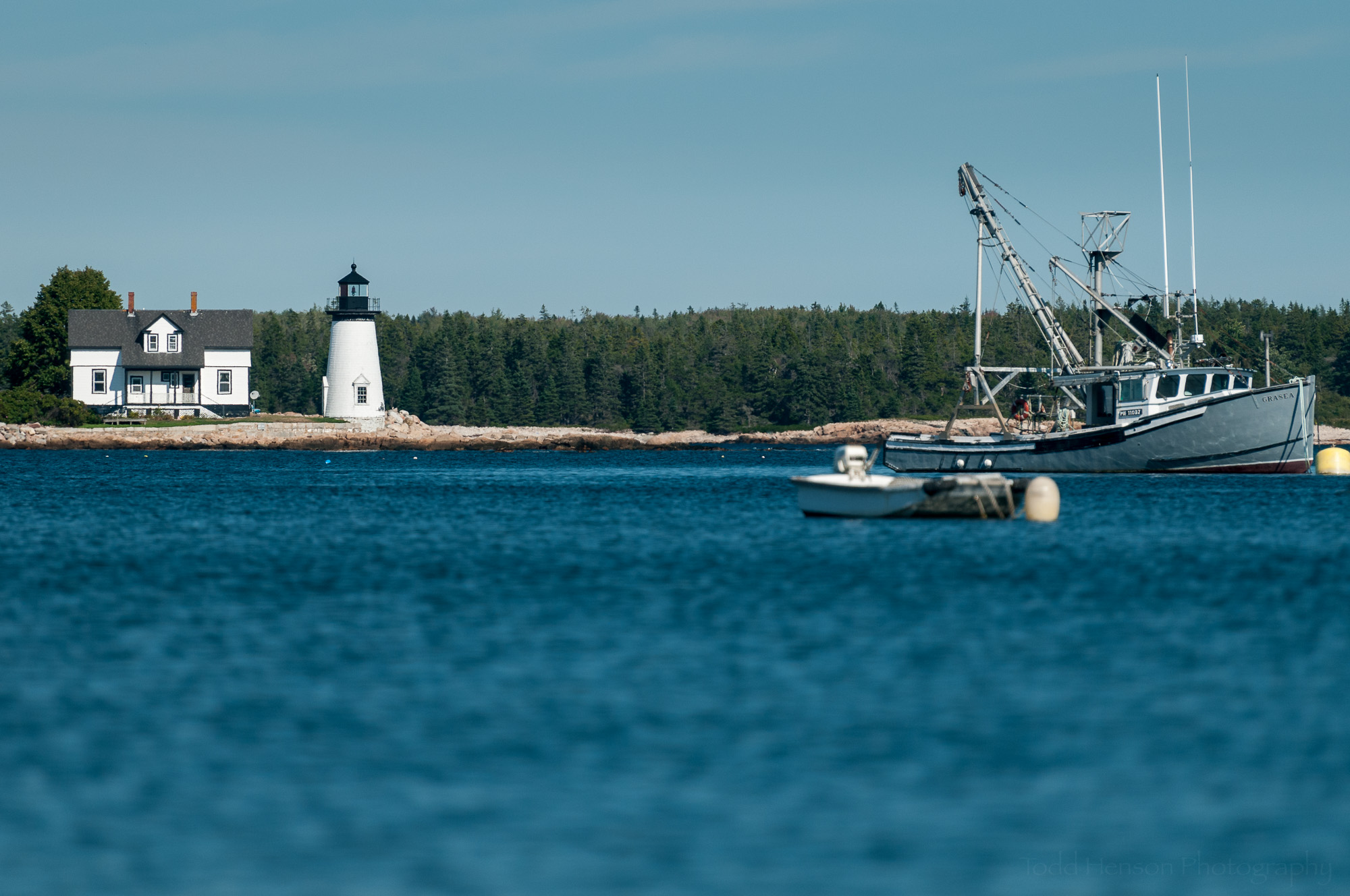 Prospect Harbor Point Light, Maine, with fishing boats in Inner Harbor, viewed from the shore of Prospect Harbor