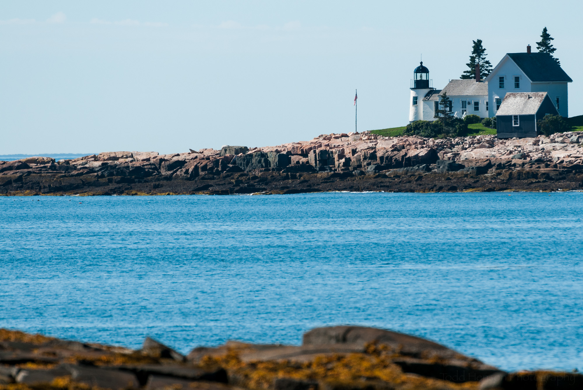 Winter Harbor Light, on Mark Island, Maine, seen from rocky coast of the Schoodic Peninsula portion of Acadia National Park