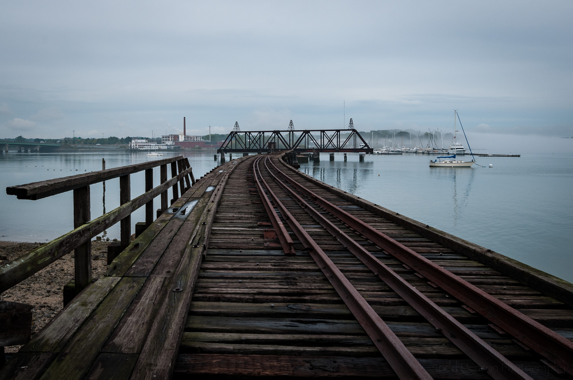 Old railroad bridge with Burnham & Morrill Company factory on distant shore
