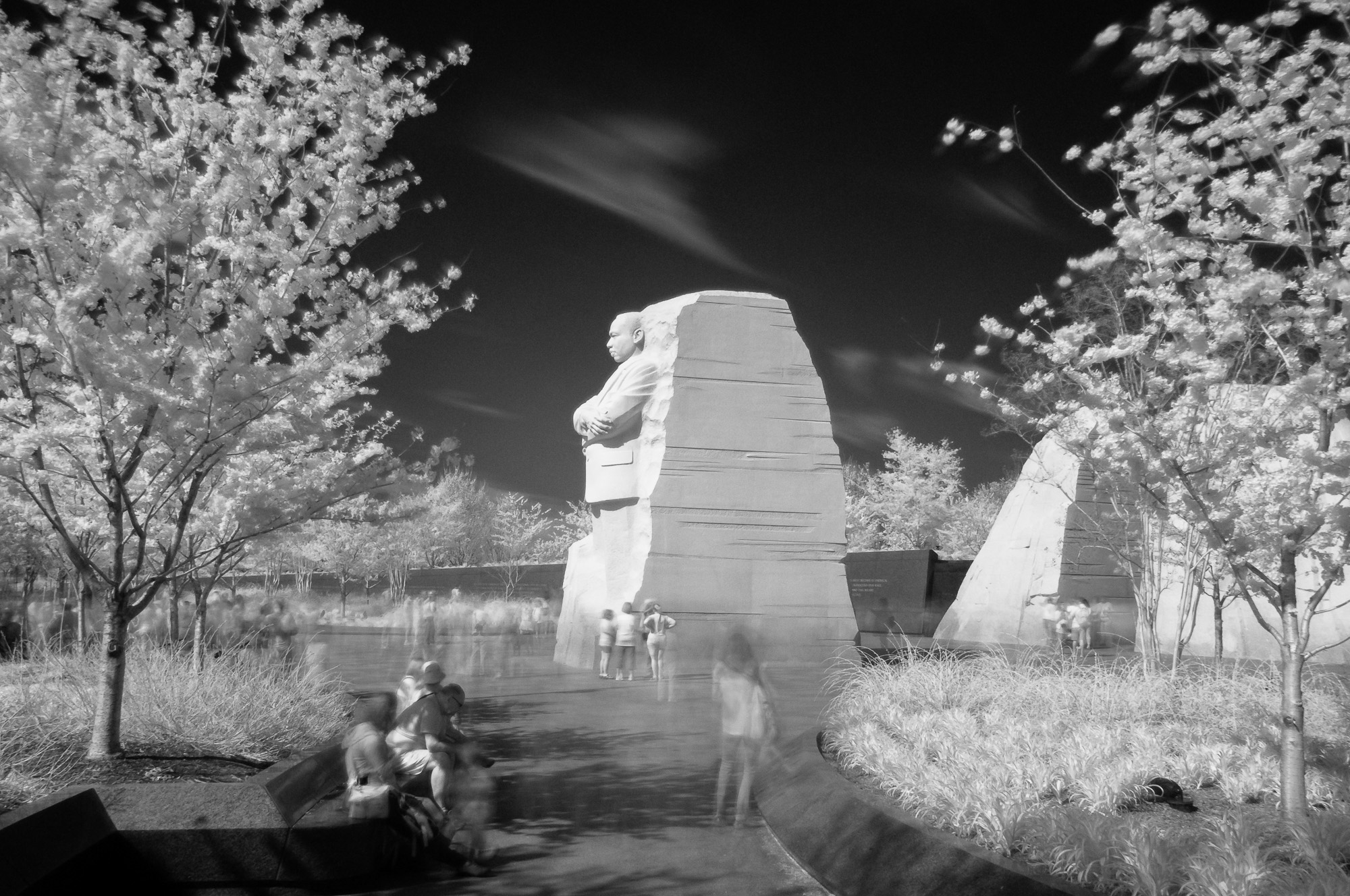Long exposure showing moving crowds around Martin Luther King, Jr. Memorial (drum major quote removed). This photograph is an Infrared black and white.