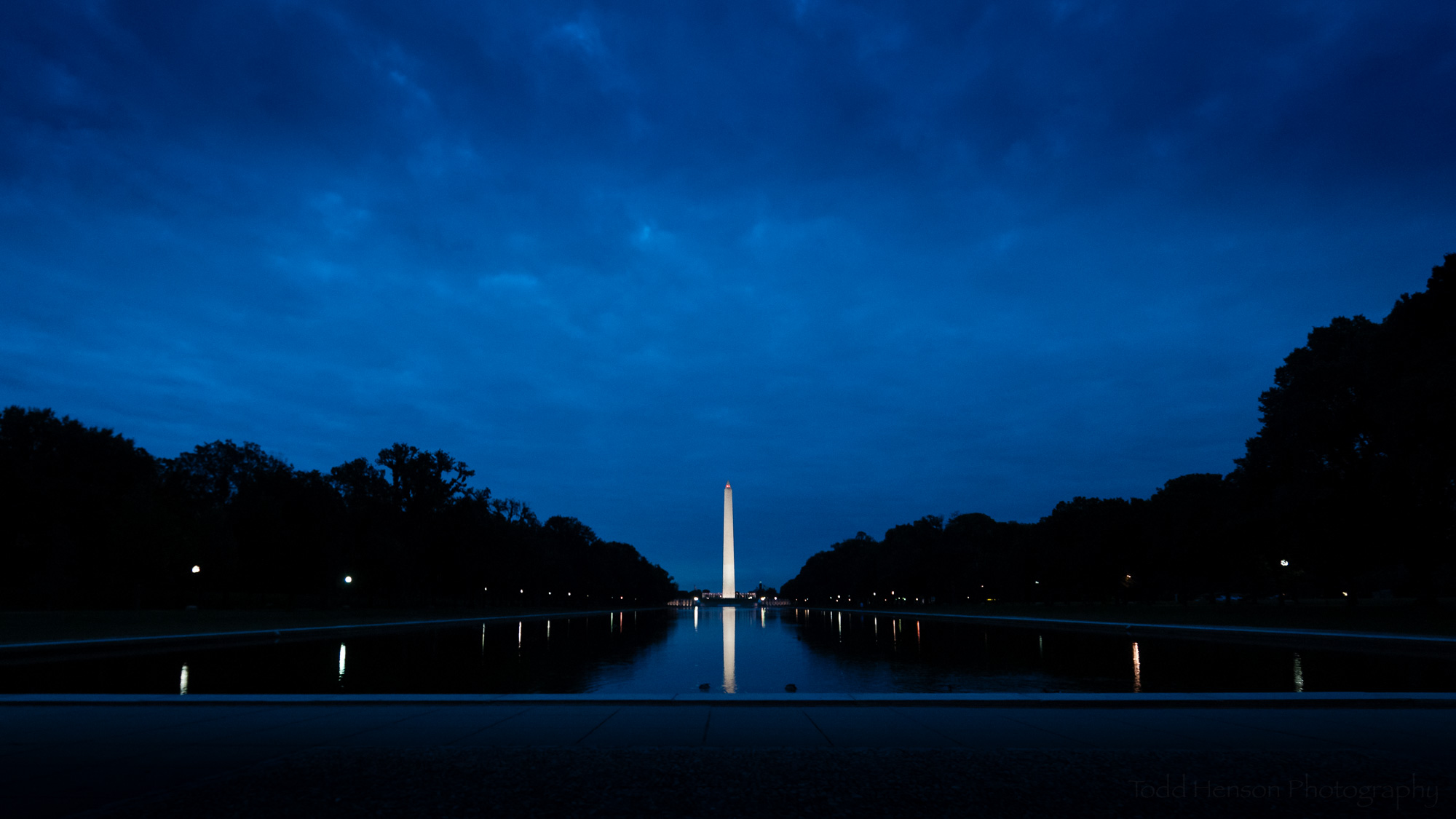 Low angle view of the Washington Monument and the Reflecting Pool during the blue hour before sunrise.